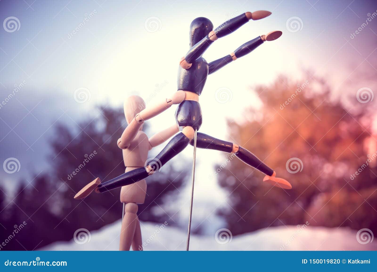 Hölzernes Mannequin, das anderem Mannequin hilft zu springen