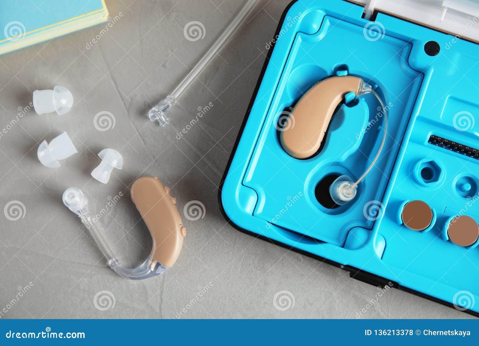 Hörapparater och fall på den gråa tabellen