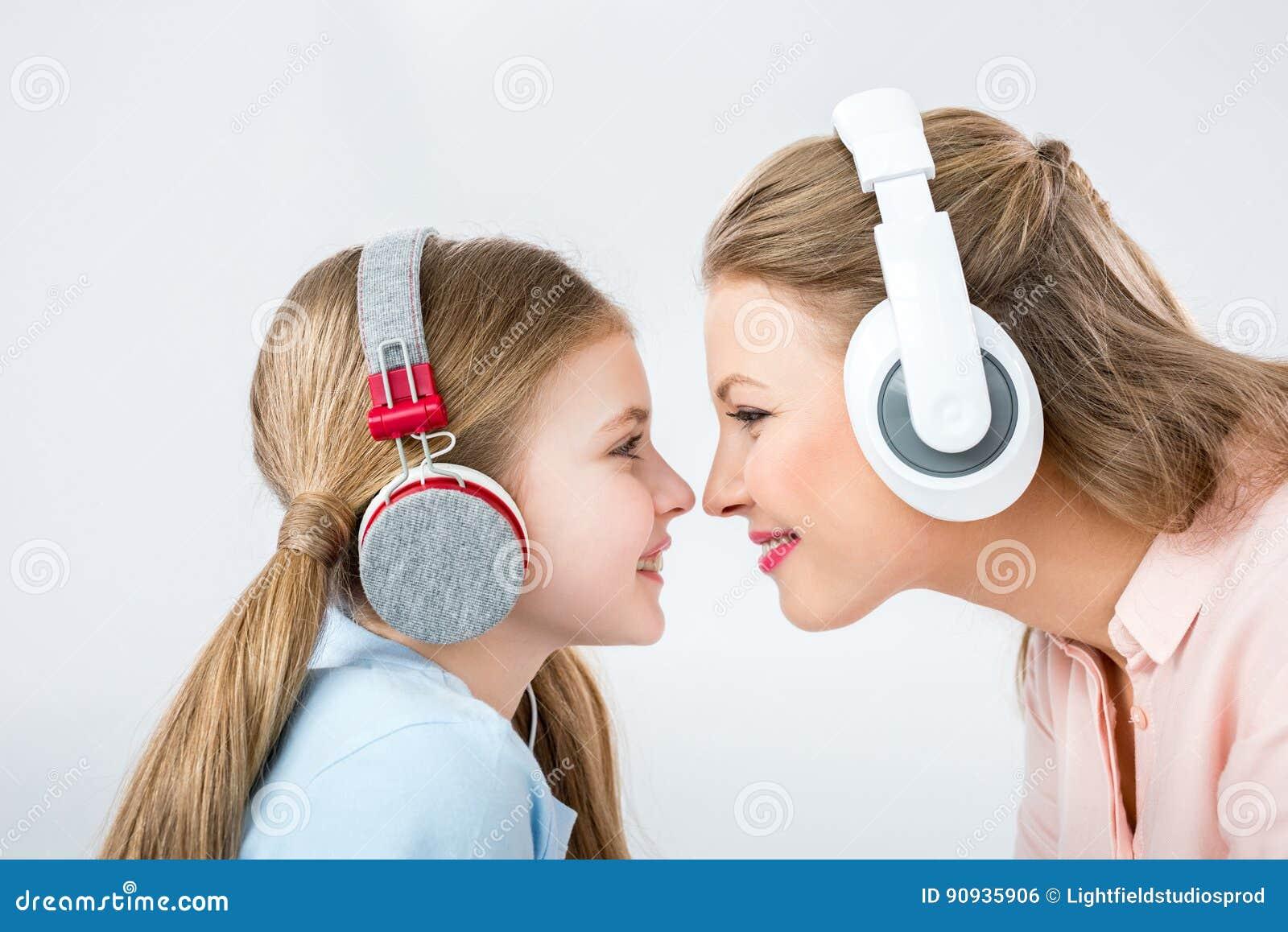 Hörende Musik der Mutter und der Tochter mit Kopfhörern im Studio