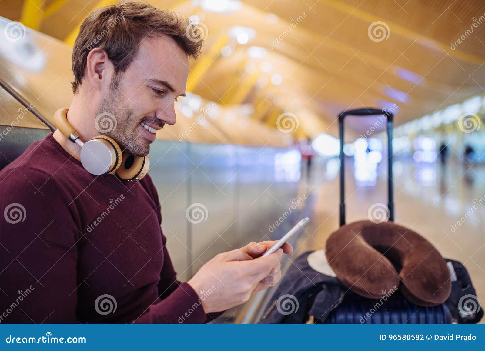 Hörende Wartemusik des jungen Mannes und mit Handy an