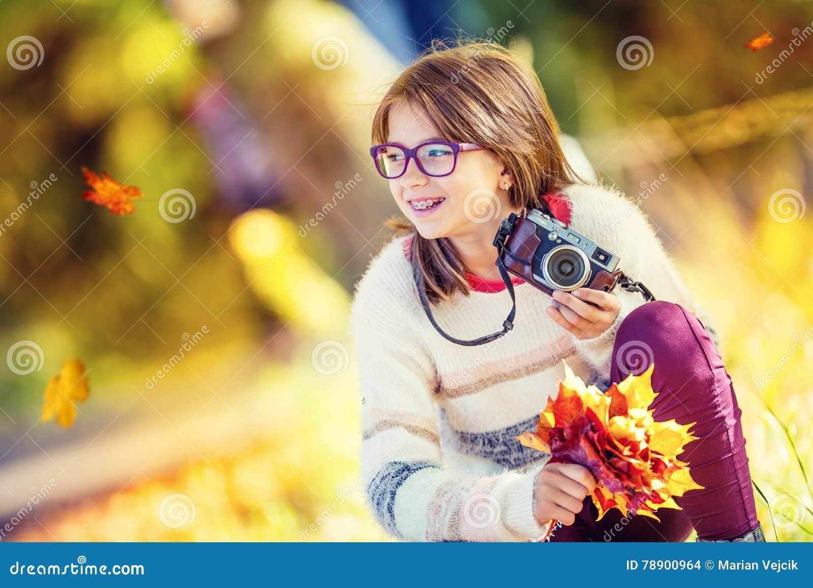 Höst Time Den tonårs- attraktiva gulliga unga flickan med höstbuketten och den retro kameran Ung flickafotografhöstsäsong