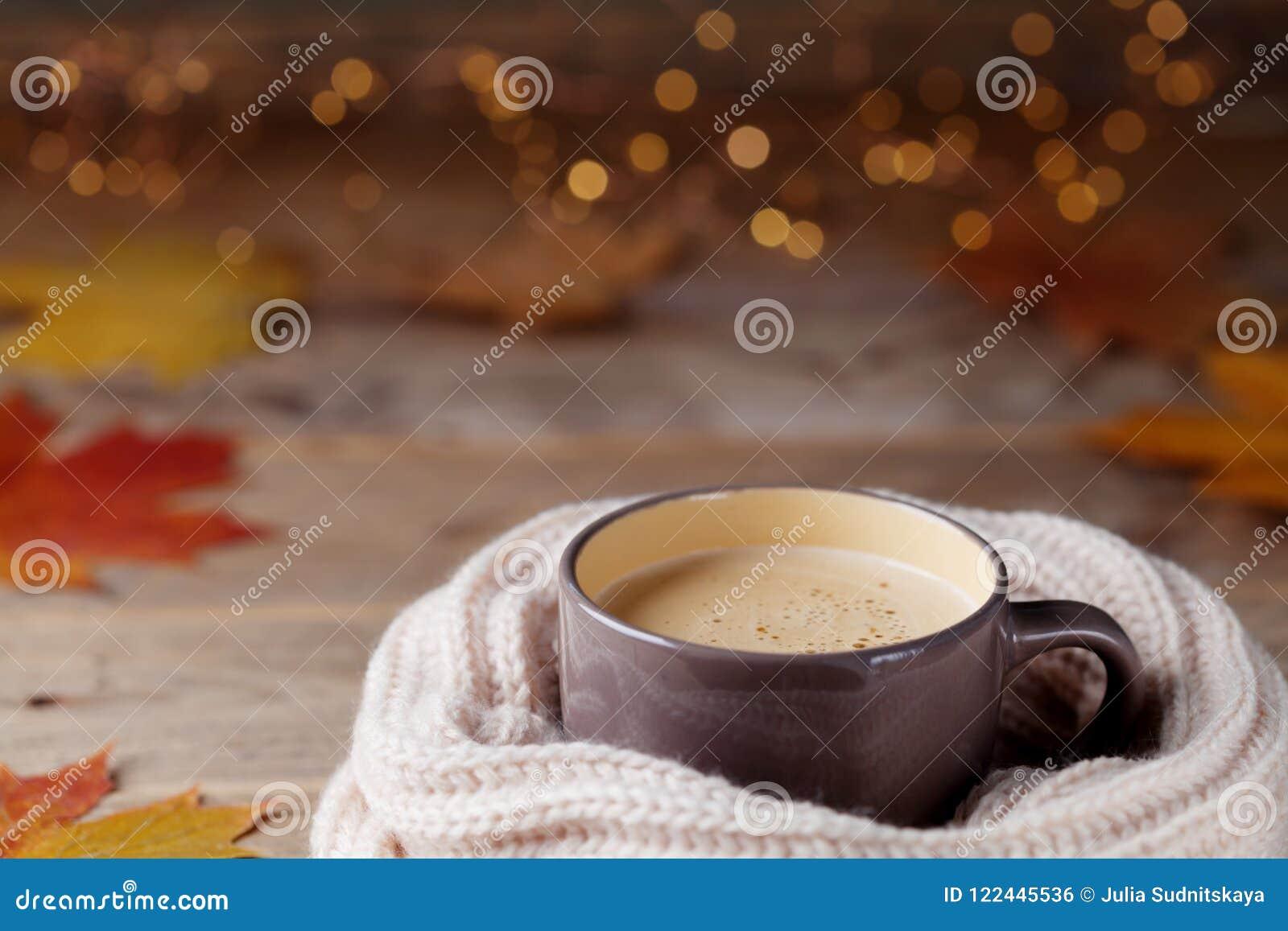 Höstbakgrund från koppen av kakao eller kaffe i stucken halsduk på trätabellen dekorerade med nedgångsidor Hemtrevlig varm drink