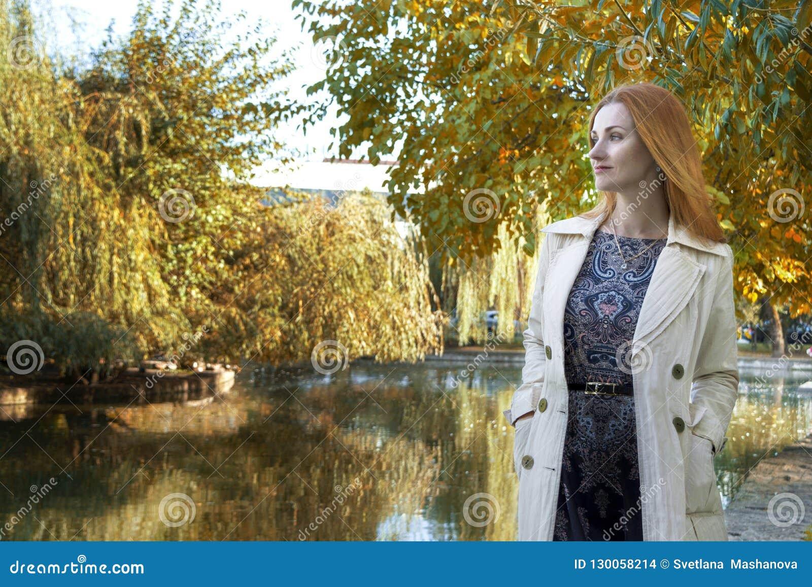Höstbakgrund, sjön, flickan ser in i avståndet