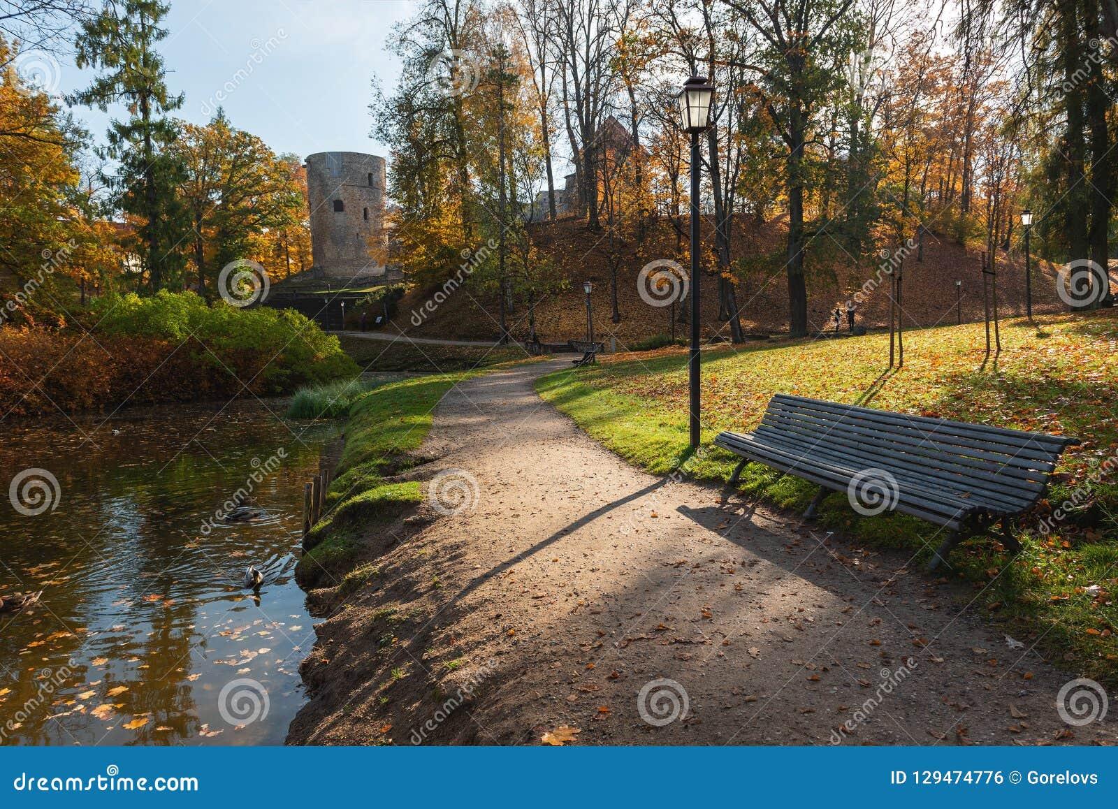 Hösten parkerar med promenad längs sjön i den Cesis staden, Lettland