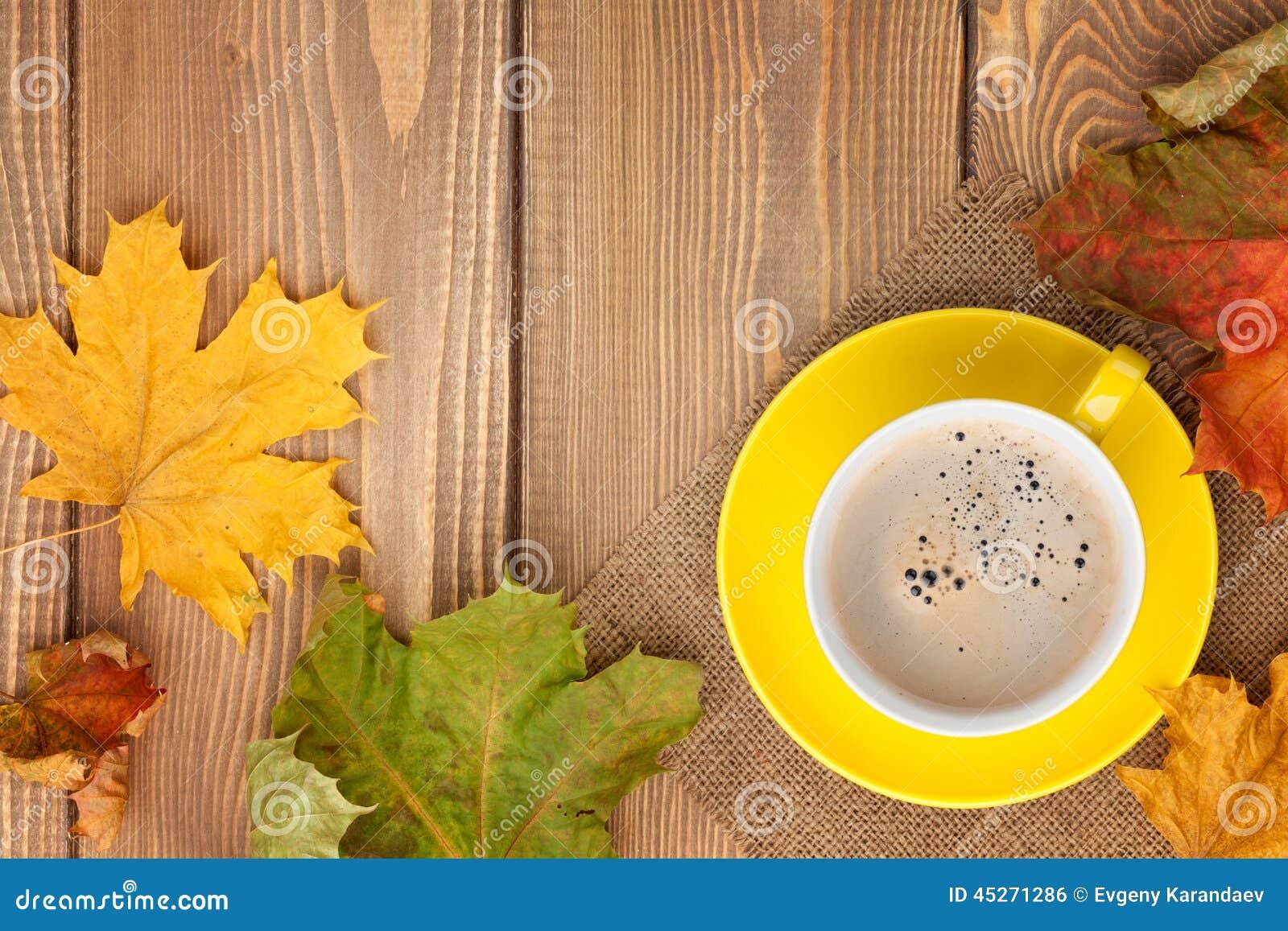 Höstsidor och kaffekopp över wood bakgrund