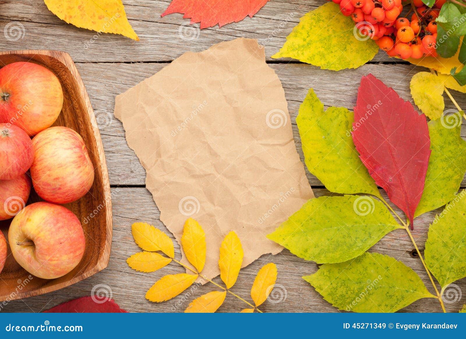 Höstsidor, rönnbär och äpplen över wood bakgrund