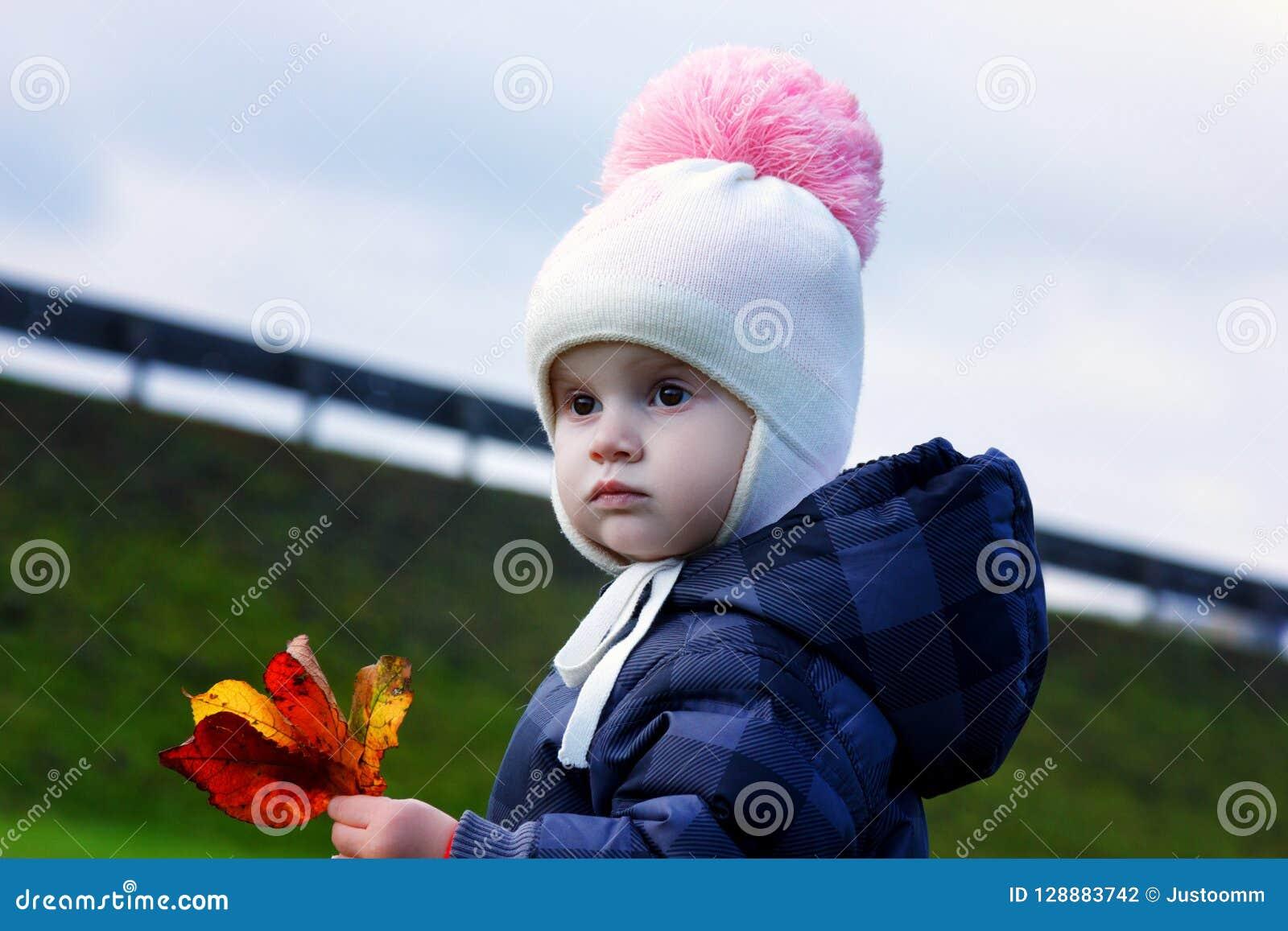 Höststående av en gullig liten flicka i ett mörkt omslag I händerna av en bukett av gula sidor solig höstdag