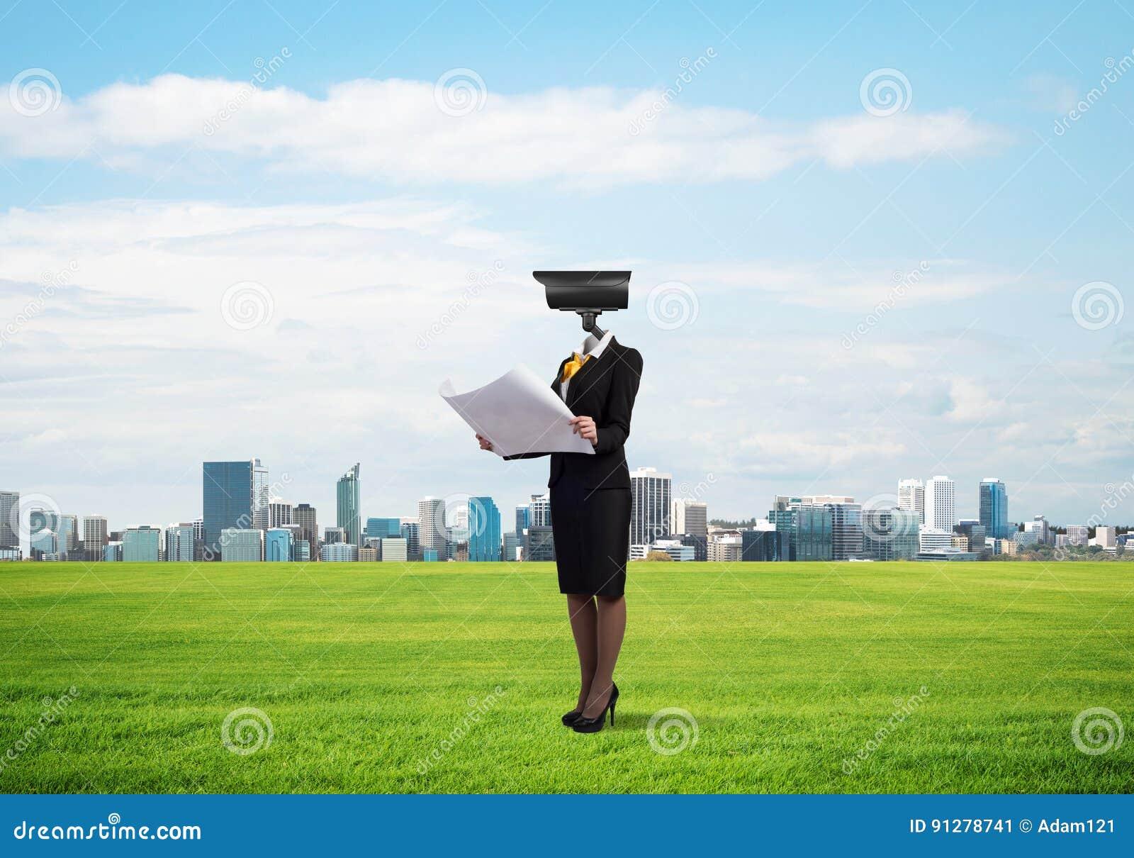 Hövdat kvinnaanseende för kamera på grönt gräs mot modern cityscape