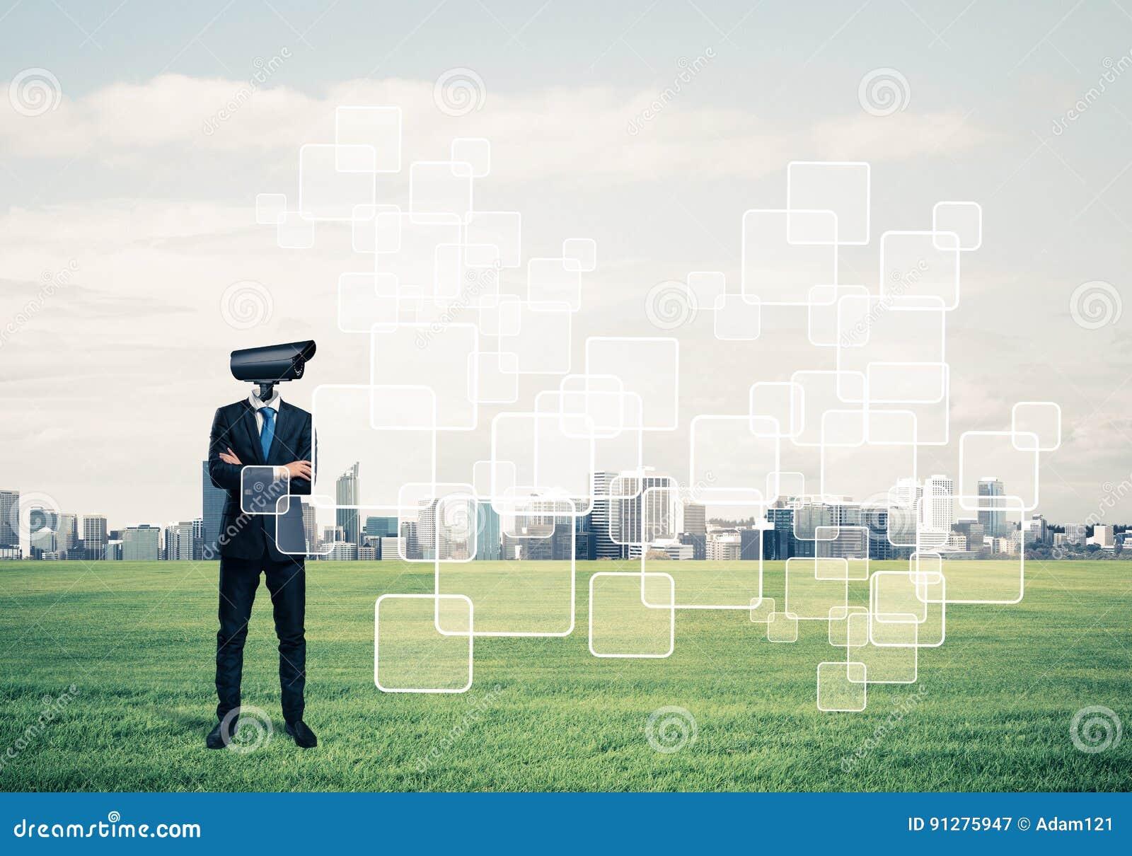 Hövdat mananseende för kamera på grönt gräs mot modern citysca