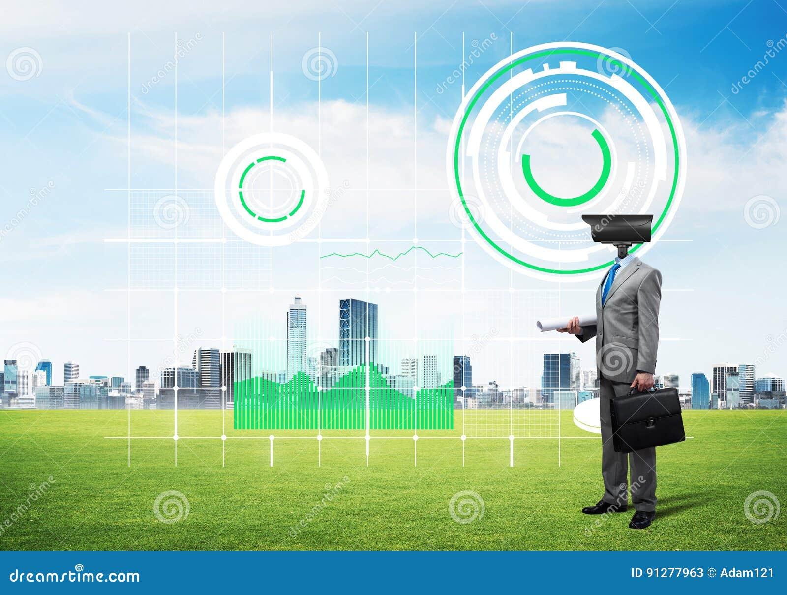 Hövdat mananseende för kamera på grönt gräs mot modern cityscape