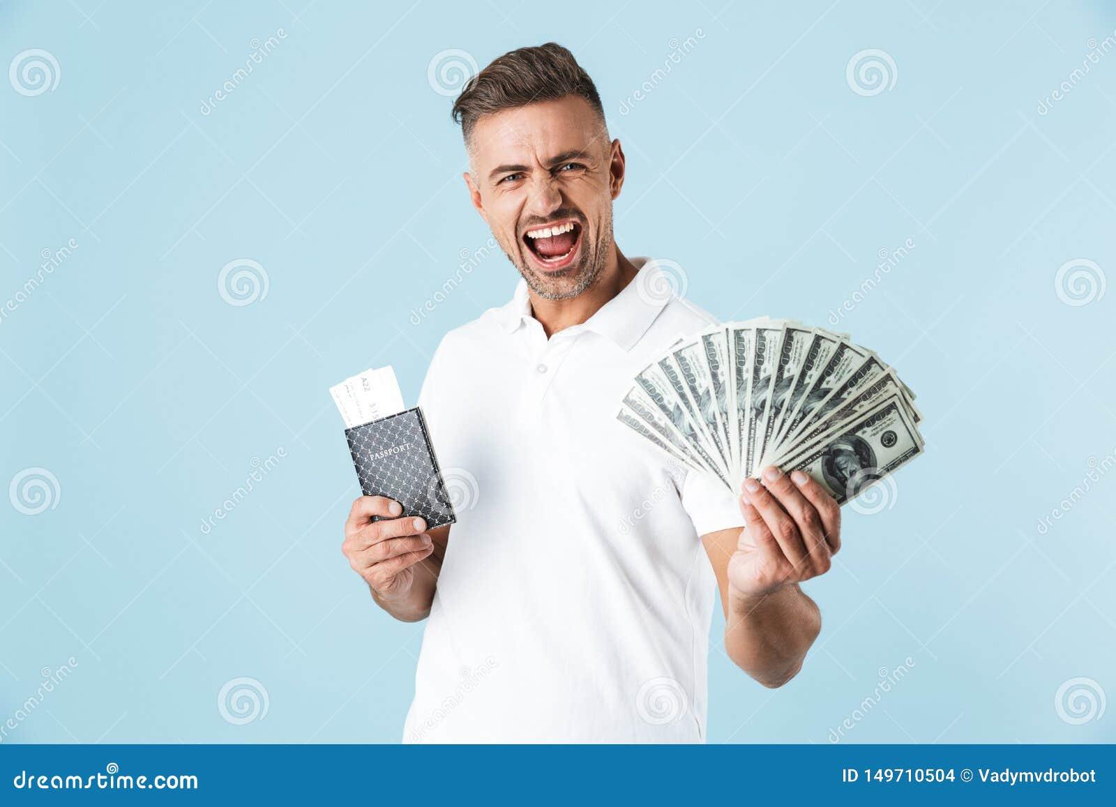 Hübsche aufgeregte emotionale erwachsene Mannaufstellung lokalisiert über blauem Wandhintergrund-Holdingpaß mit Karten und Geld