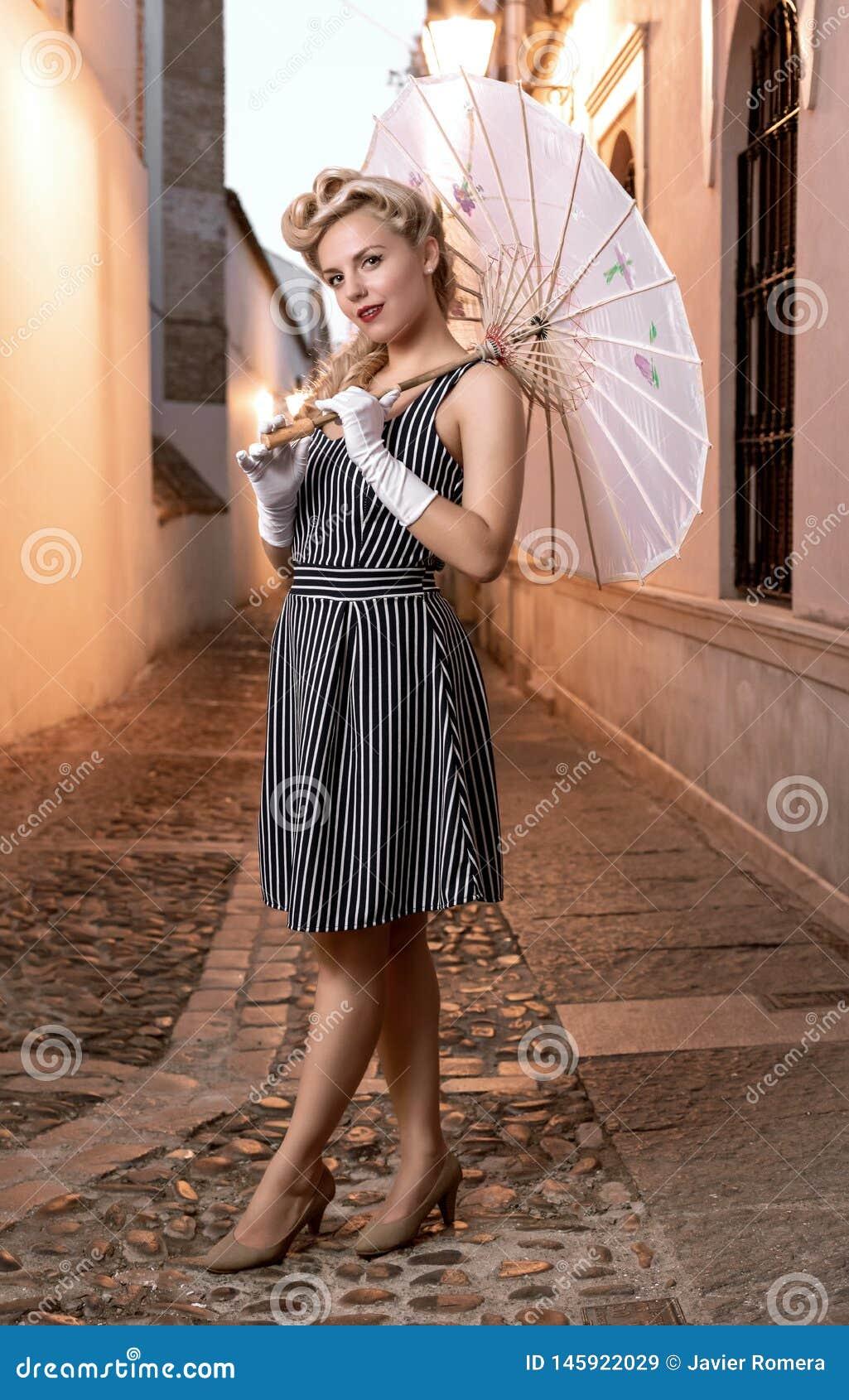 Hübsche Blondine im Retrostil, der mit einem japanischen Regenschirm aufwirft