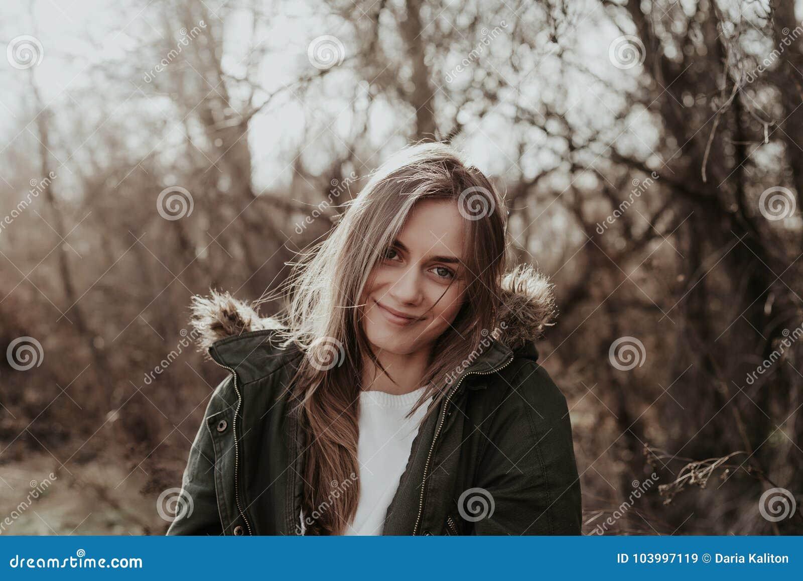 Hübsche Frau in der warmen Jacke mit Pelz posint an der Kamera im Freien