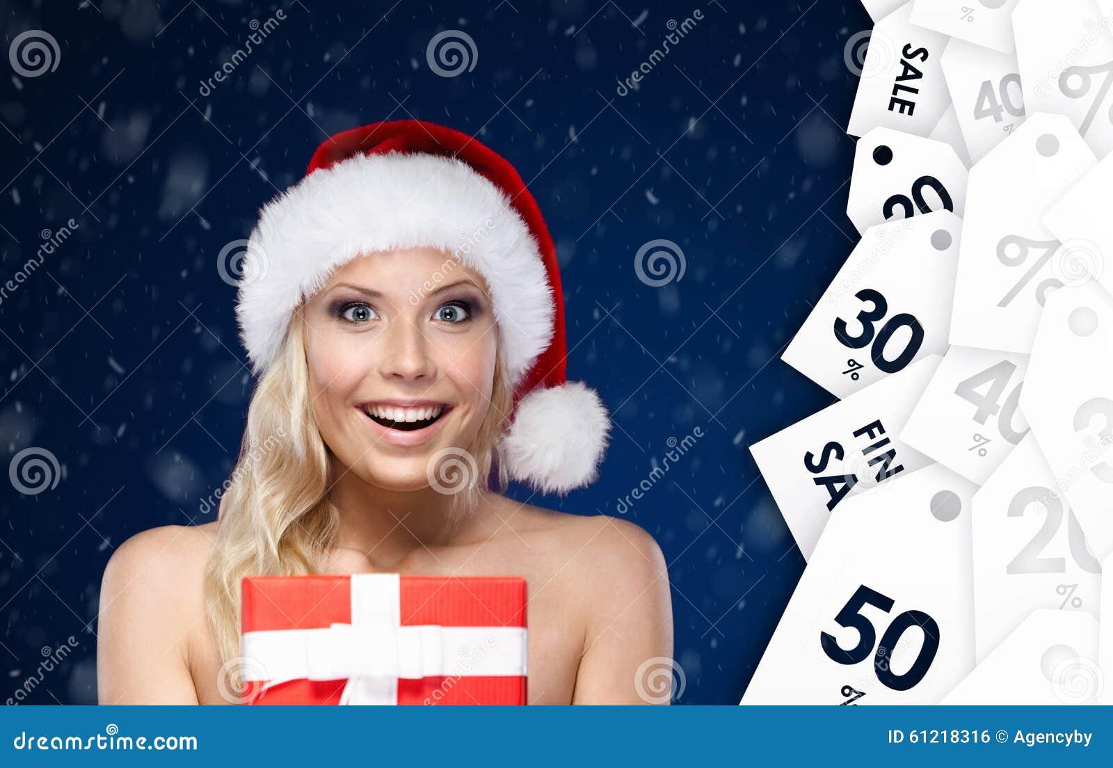 Hübsche Frau in der Weihnachtskappe übergibt das Geschenk, das mit rotem Papier eingewickelt wird