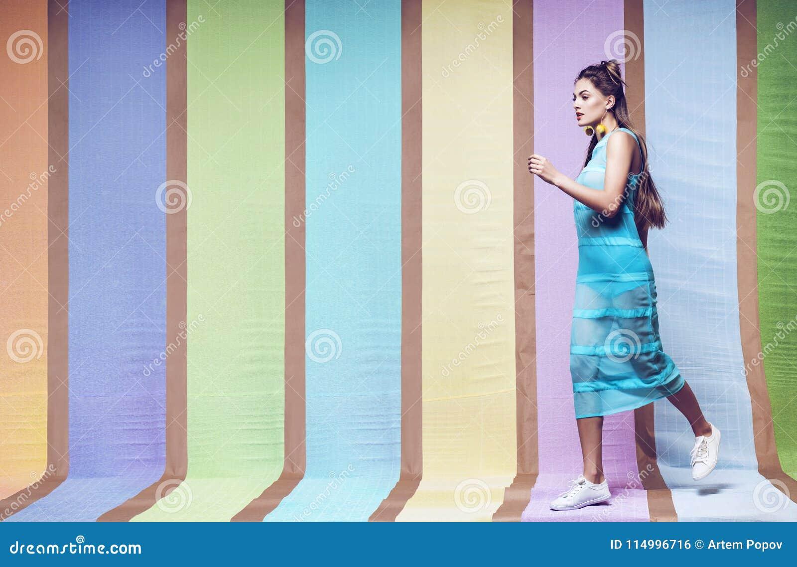 hübsche frau, die in blaues kleid und in weiße schuhe geht