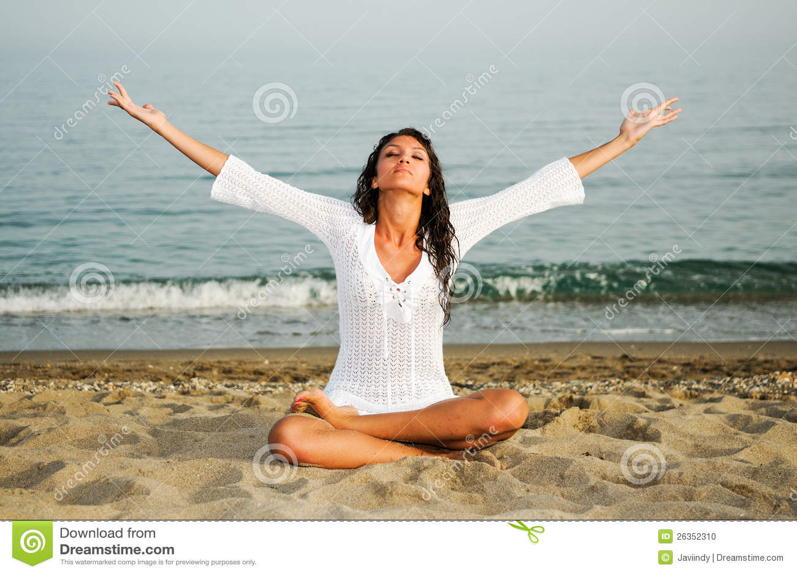 Hübsche Frau, die Yoga auf dem Strand tut