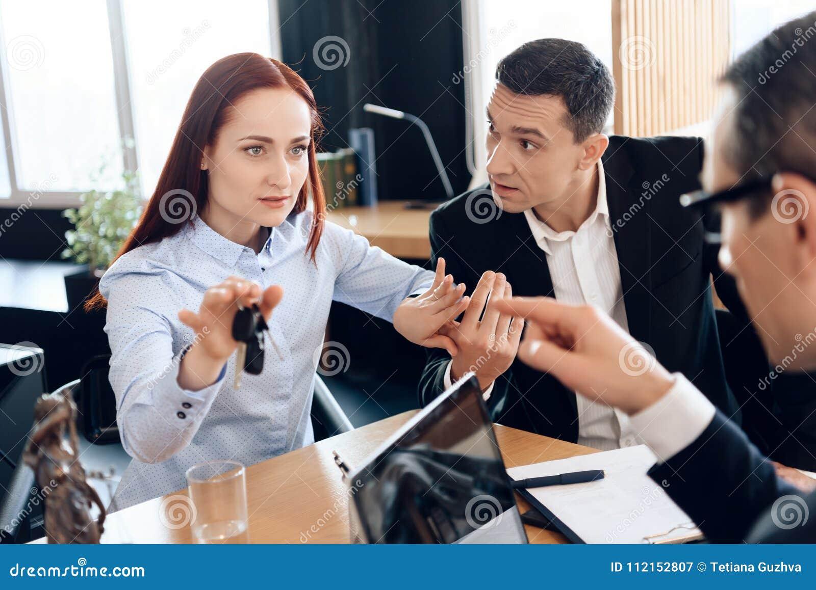 Hübsche Frau hält an die Fingerschlüssel, die nahe bei erwachsenem Mann in Rechtsanwalt ` s Büro sitzen
