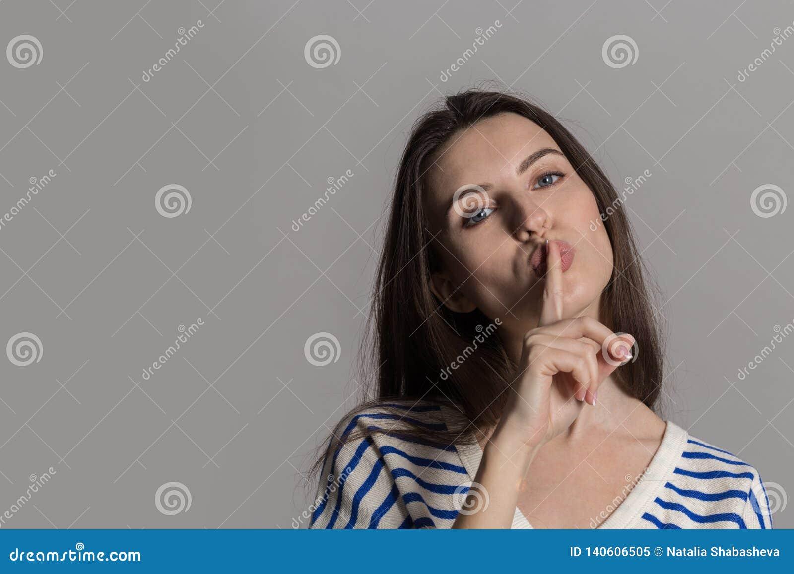 Hübsche Frau mit dem flaumigen Haar, zufällig gekleidet gegen eine graue Studiowand