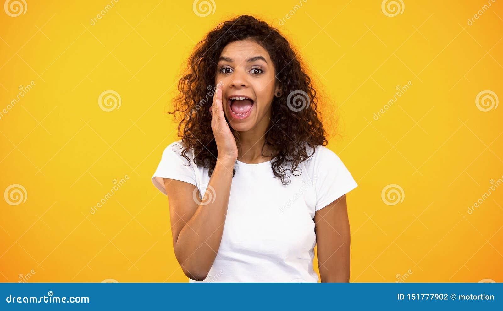 Hübsche gelockte Frau im weißen T-Shirt, das Geheimnissen, Klatsch, Kommunikation sagt