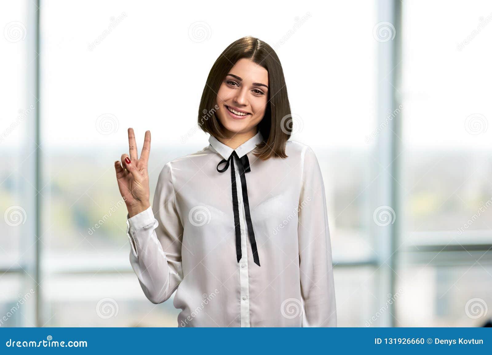 Hübsche Geschäftsfrau, die Frieden gestikuliert