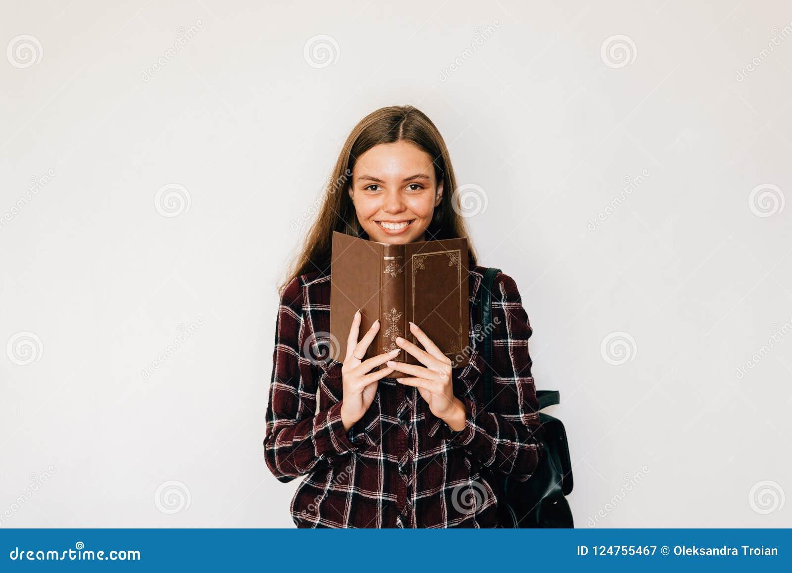 Hübsche JugendlichStudentin mit Buch in ihren Händen, die Gesicht mit dem Kopienraum- und -WEISShintergrundlächeln verstecken