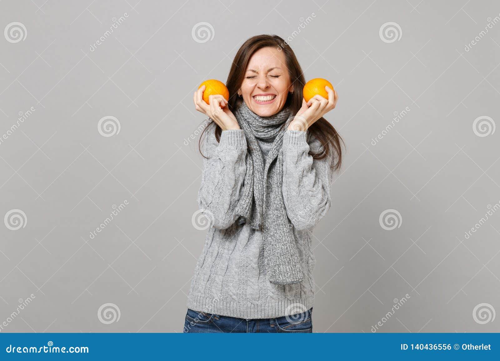 Hübsche junge Frau in der grauen Strickjacke, Schal mit den geschlossenen Augen, die Orangen lokalisiert auf grauem Wandhintergru