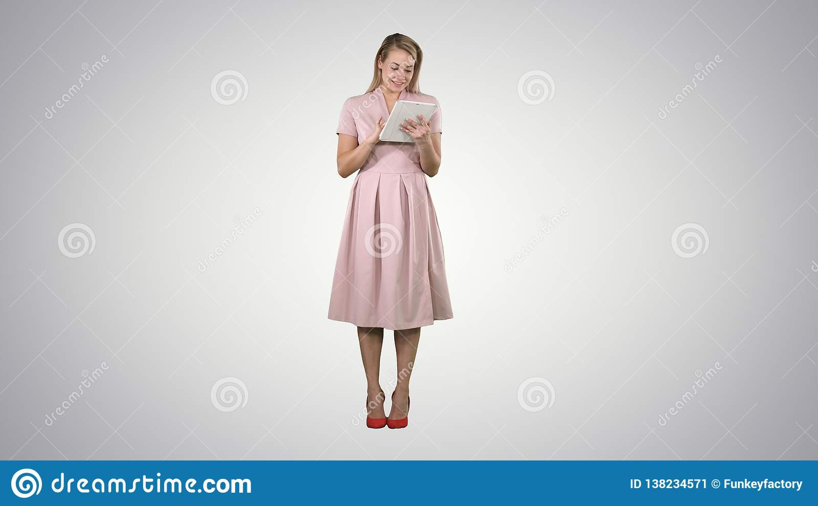 Hübsche junge Frau in der rosa Kleiderholdingtablette und Schauen auf ihm auf Steigungshintergrund