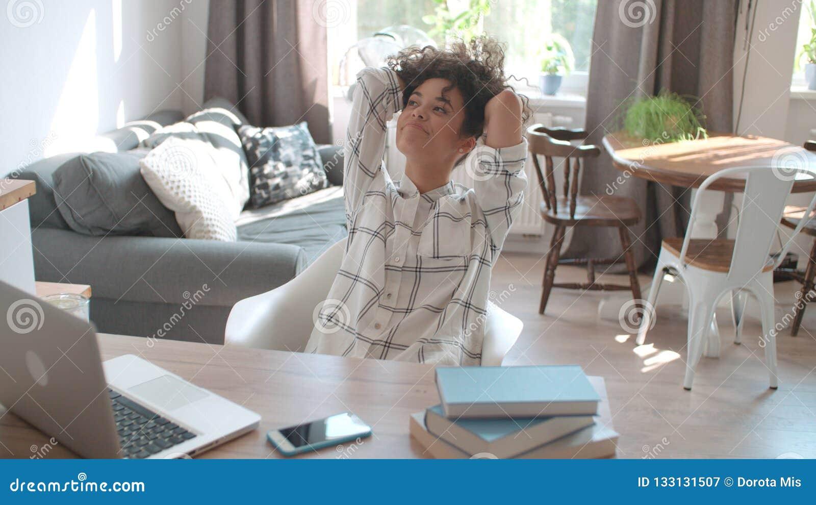 Hübsche junge Frau, die an dem modernen Laptop zu Hause umgeben durch Bücher arbeitet
