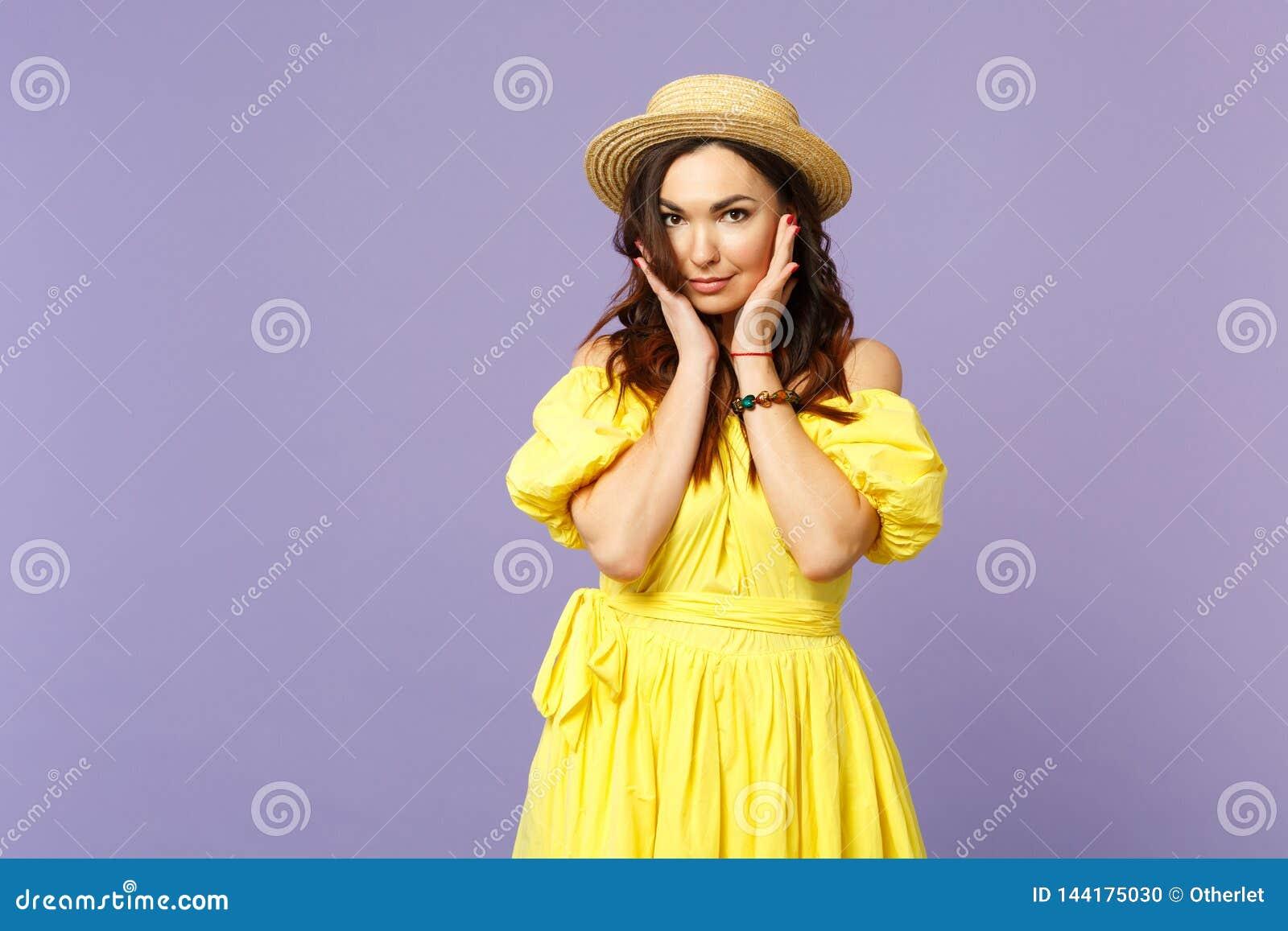 Hübsche junge Frau im gelben Kleid, Sommerhut setzte Hand sützen auf dem Kinn und schaute Kamera auf Pastellveilchen