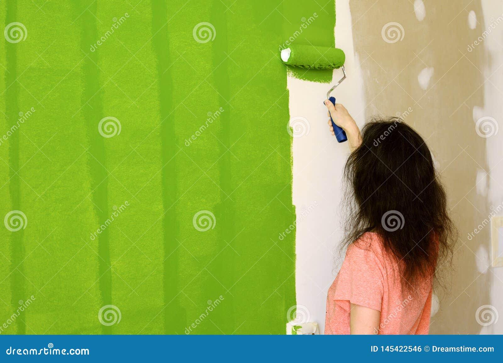 Hübsche junge Frau im rosa T-Shirt malt enthusiastisch grüne Innenwand mit Rolle in einem neuen Haus