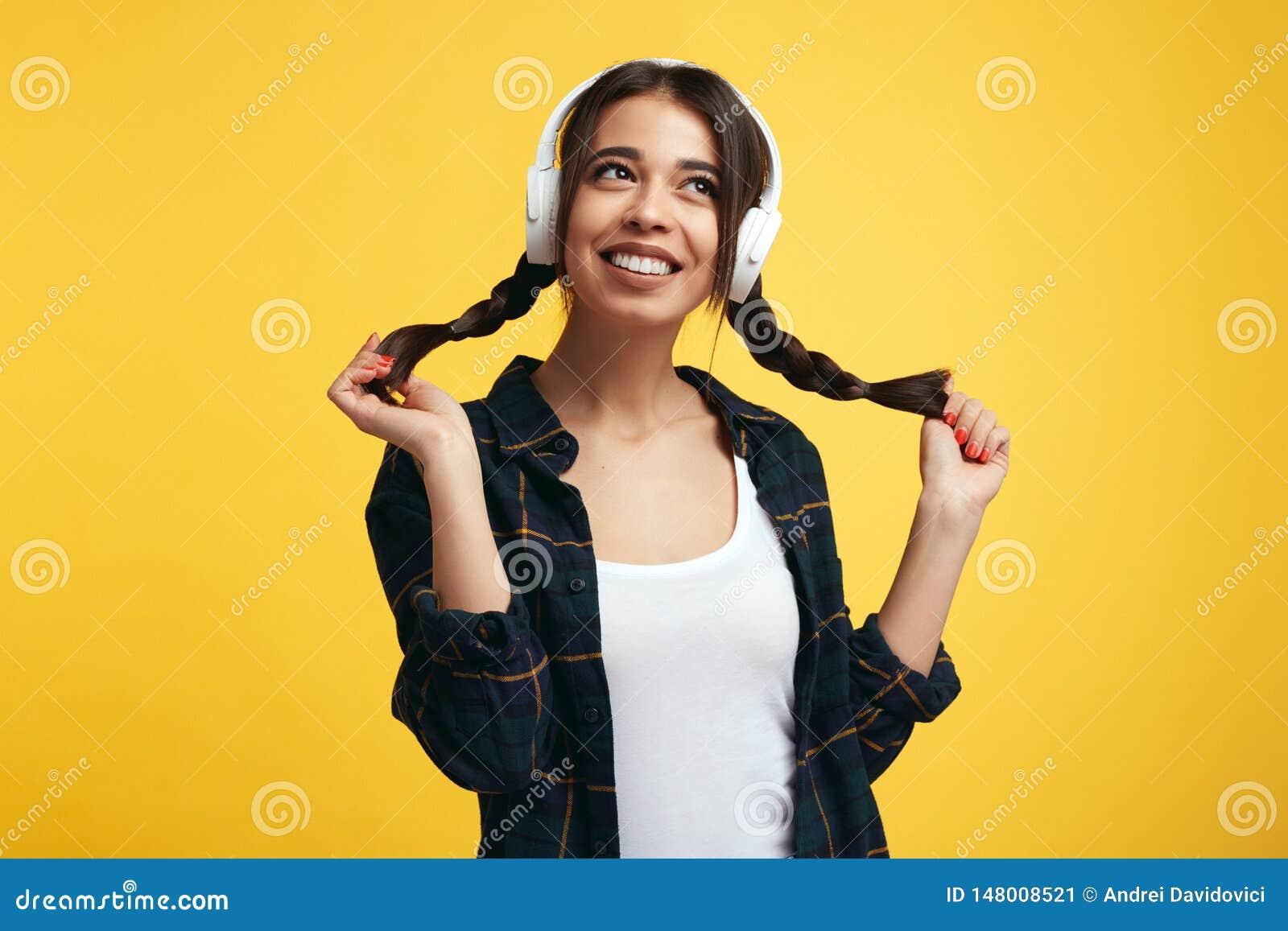 Hübsche junge Frau mit weißen Kopfhörern, hört Musik und fühlt sich froh und spielt mit ihren Pferdeschwänzen und weg schaut mit