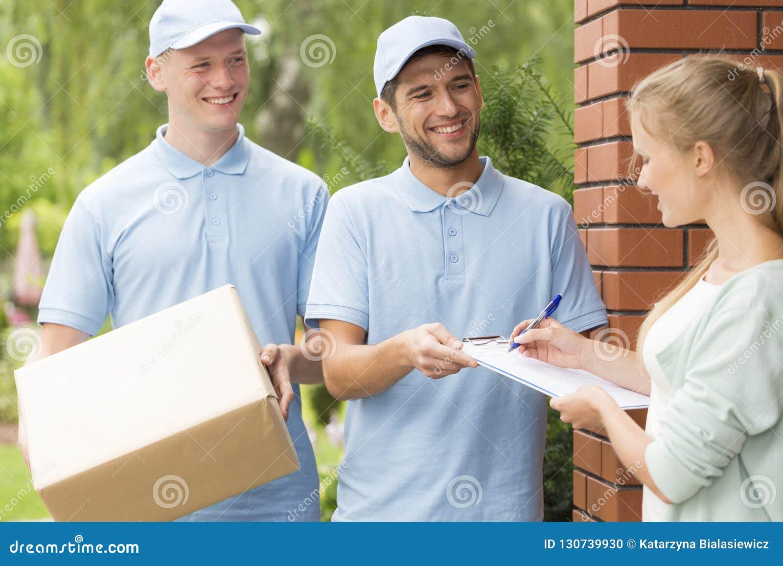 Hübsche Kuriere in den blauen Uniformen, die ein Paket an eine junge hübsche Frau liefern