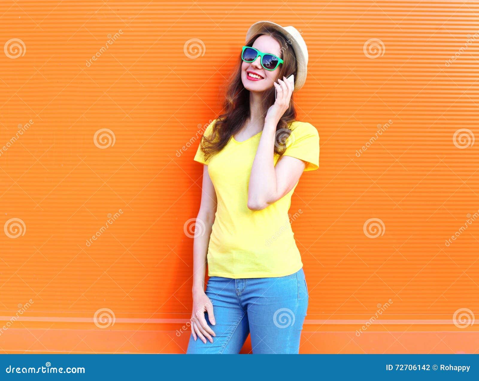 Hübsche lächelnde Frau, die auf Smartphone über bunter Orange spricht