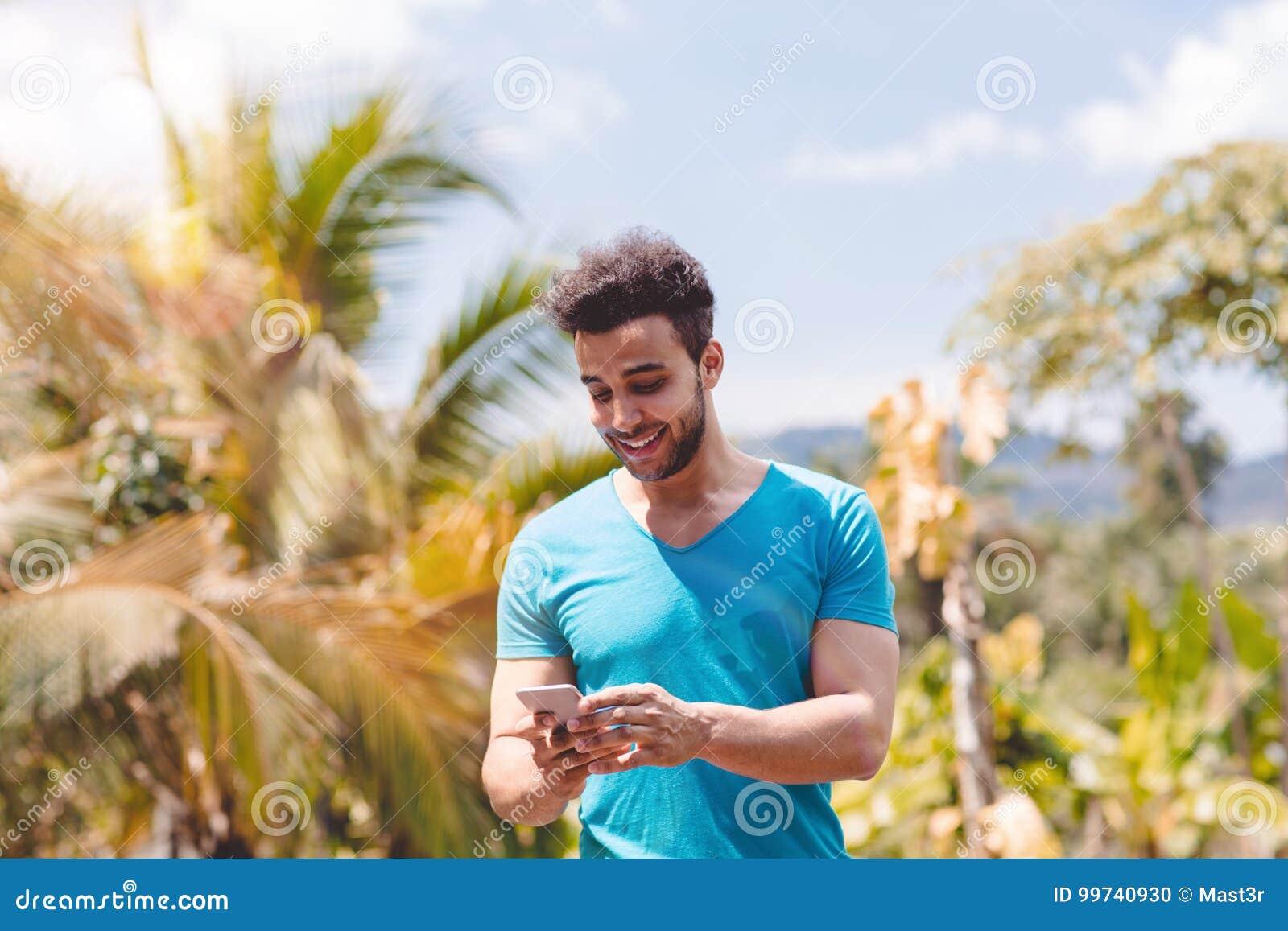 Hübsche lateinische Mann-Mitteilung mit Zellintelligentem Telefon über tropischem Forest Background, Porträt von jungem Guy Chatt