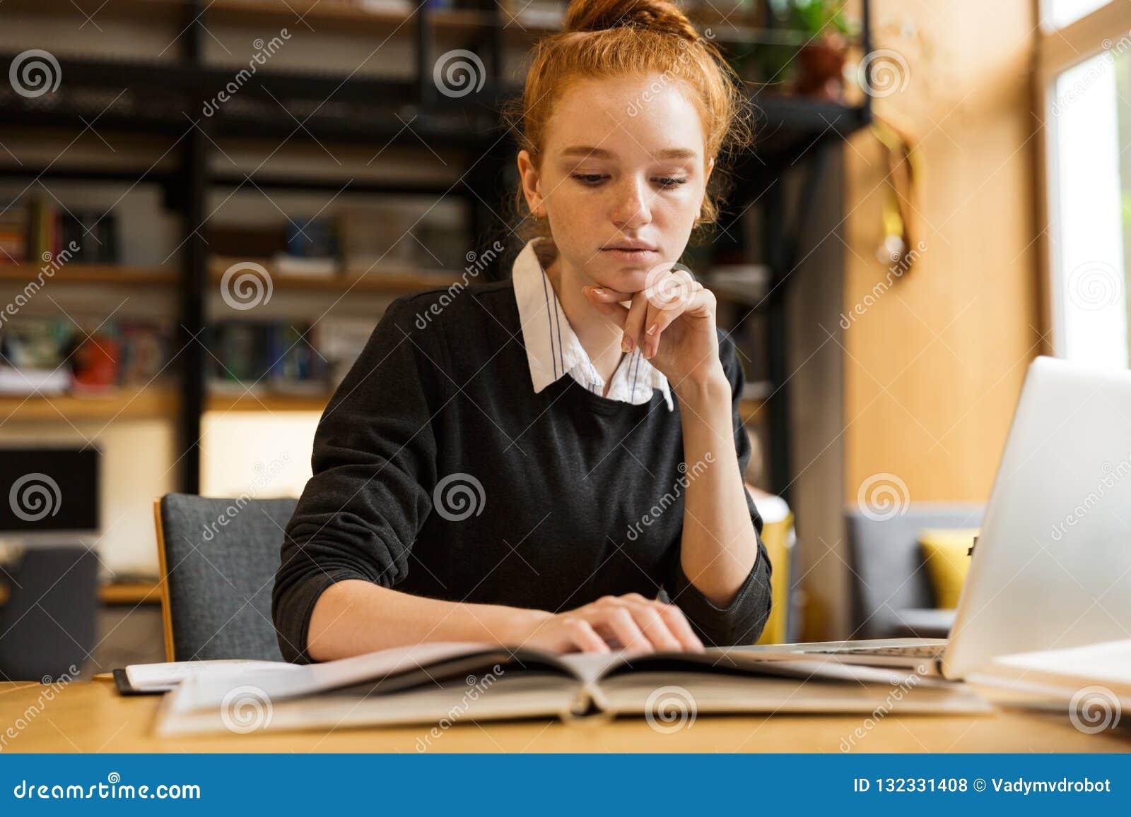 Hübsche rote behaarte Jugendliche, die Laptop-Computer verwendet