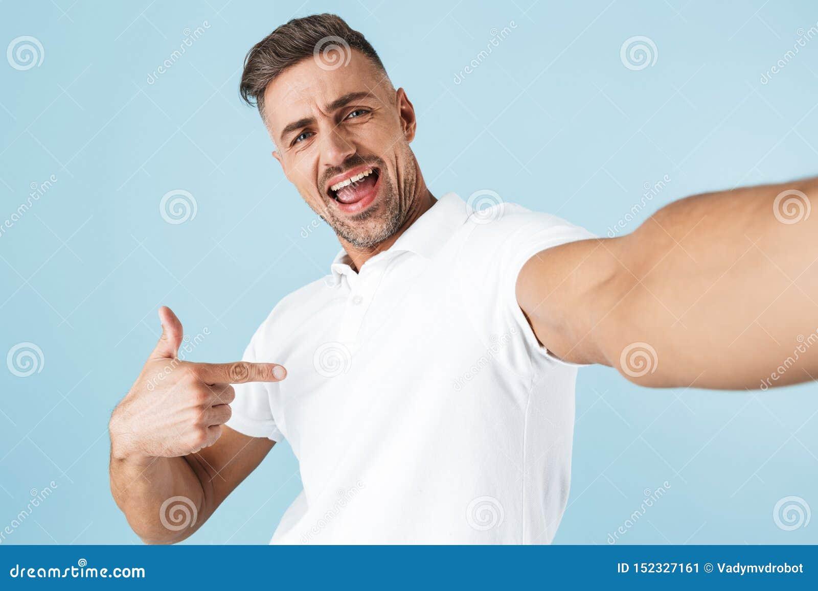 Hübsche tragende weiße Stellung T-Shirt des jungen Mannes