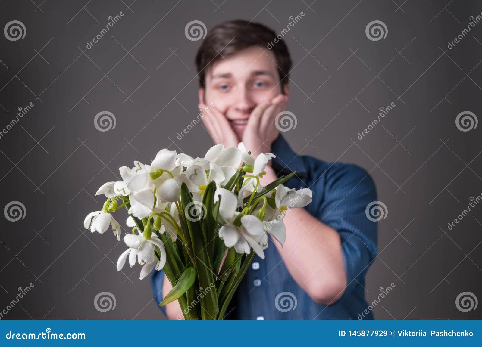 Hübscher überraschter und lächelnder junger Mann im blauen Hemd, das Backen berührt und Blumenstrauß von Schneeglöckchen auf grau
