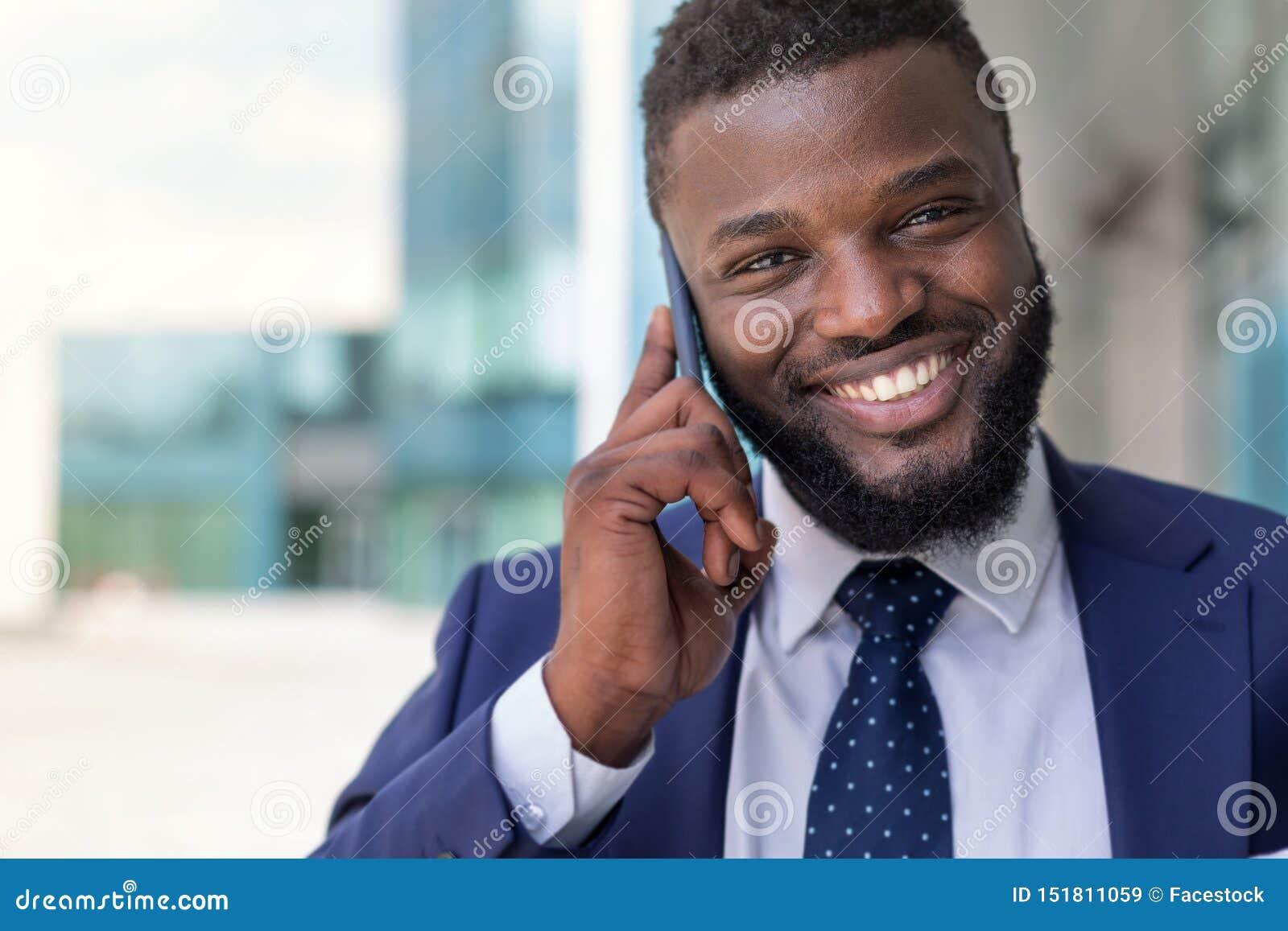 Hübscher afrikanischer Geschäftsmann in der Klage, die draußen am Telefon spricht Kopieren Sie Platz