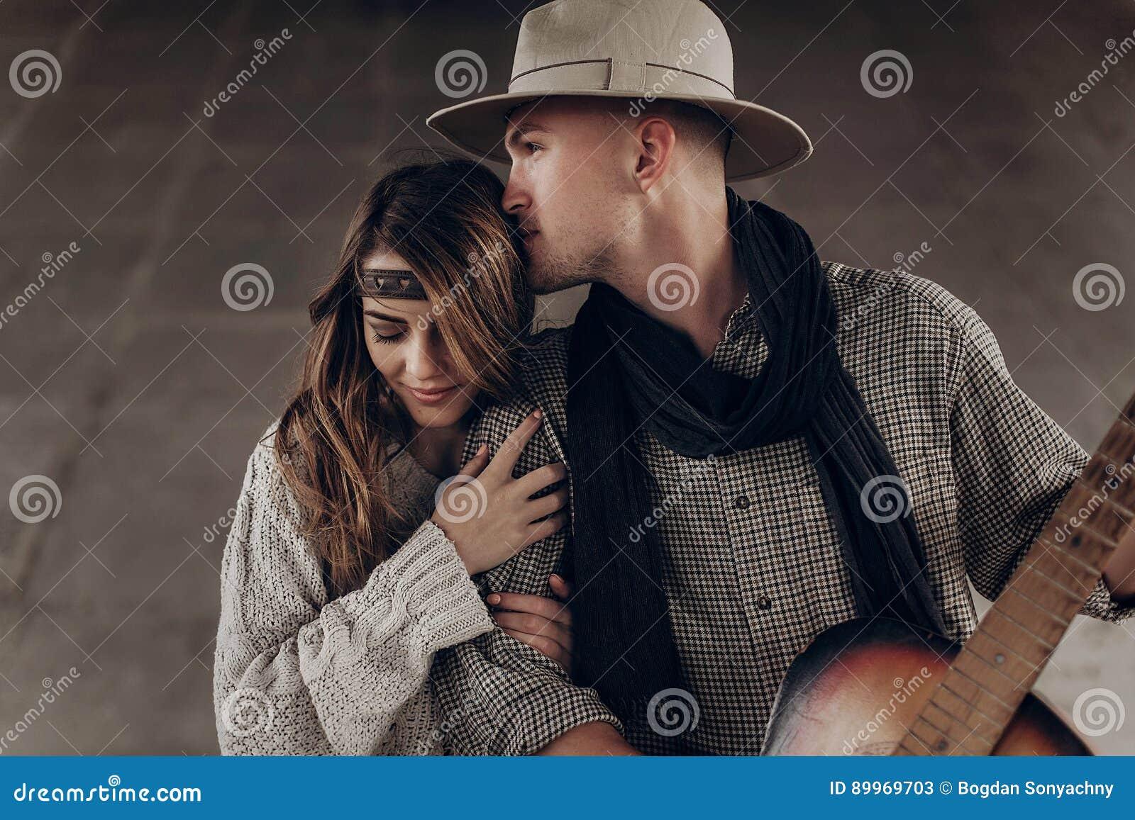 Hübscher Cowboymann mit einer Gitarre schöne indie Frau küssend