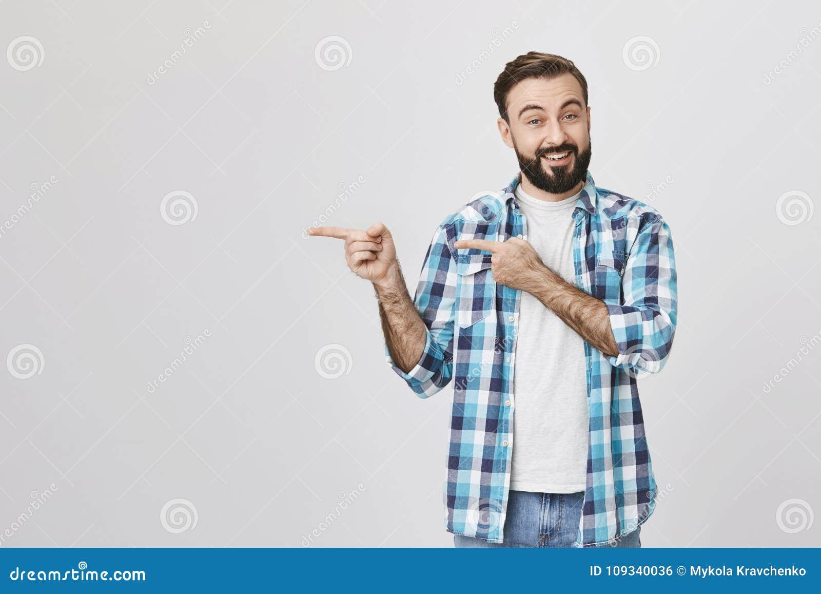 Hübscher erwachsener Gatte mit dem Bart und Schnurrbart, lächelnd und drücken Beifall beim mit zwei Händen nach links zeigen aus