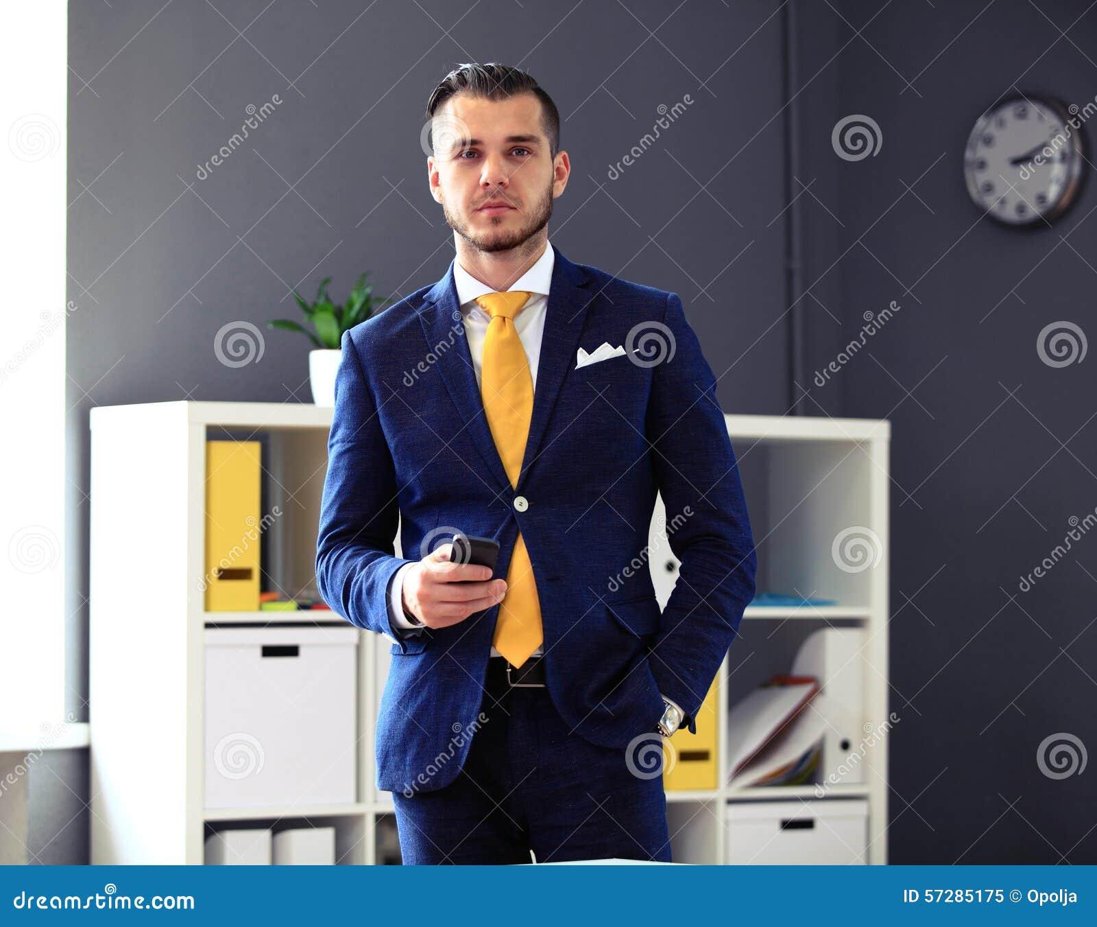 Hübscher Geschäftsmann in der Klage, die Kamera betrachtet