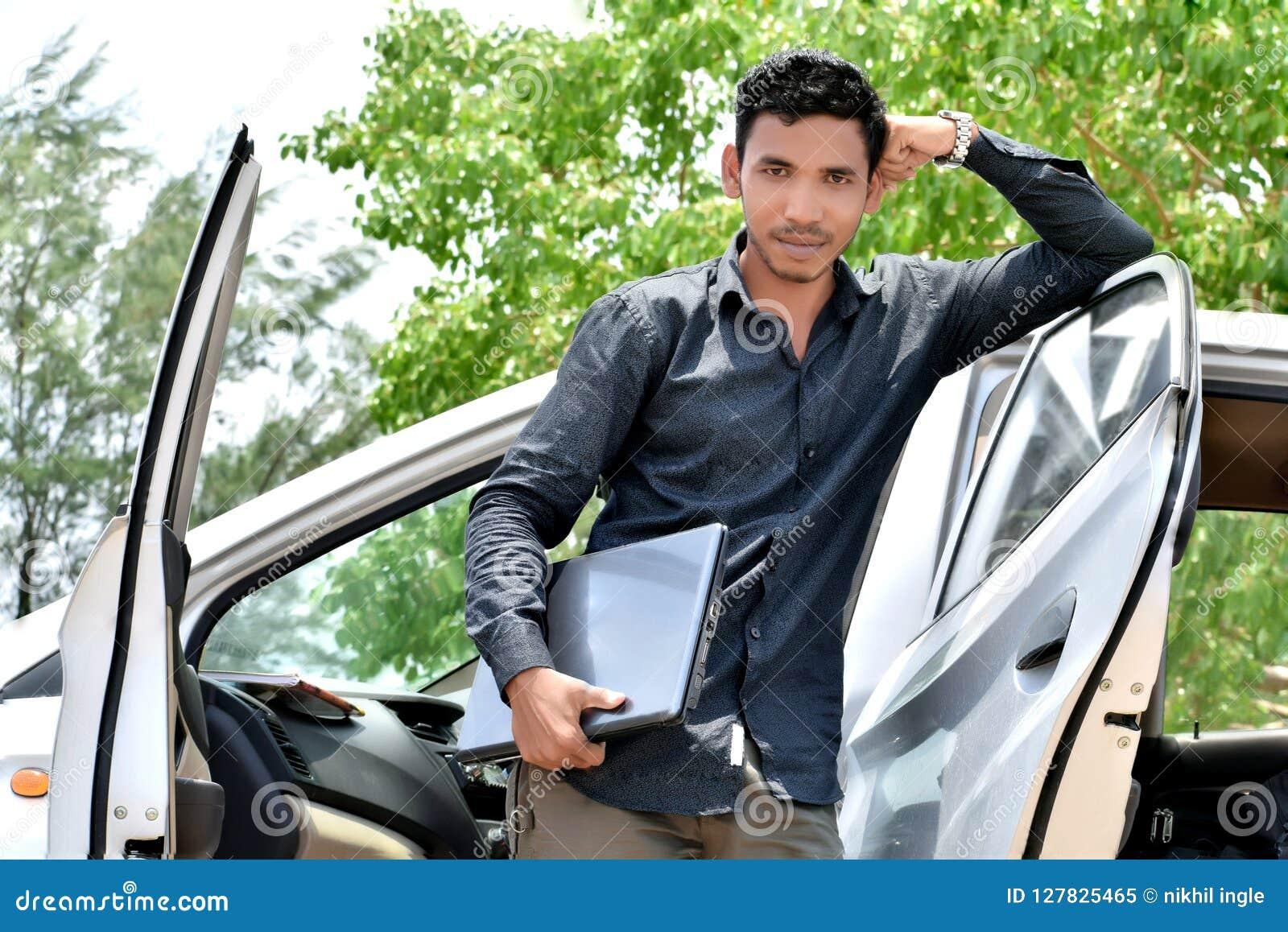 Hübscher indischer Geschäftsmann, der an Laptop mit Auto arbeitet