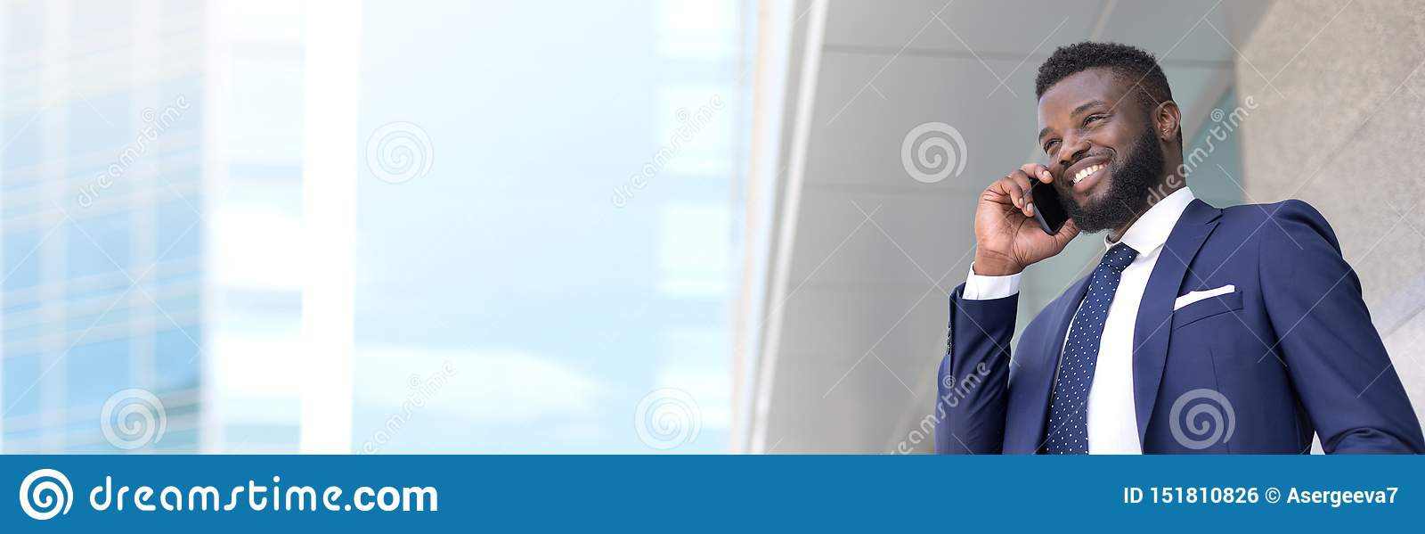 Hübscher junger afrikanischer Geschäftsmann, der draußen mit einem Kunden am Handy mit Kopienraum spricht
