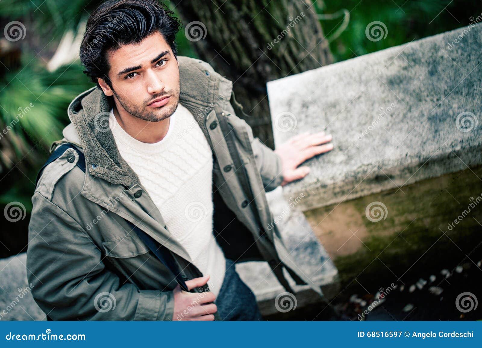 Hübscher junger italienischer Mann, stilvolles Haar und Mantel draußen