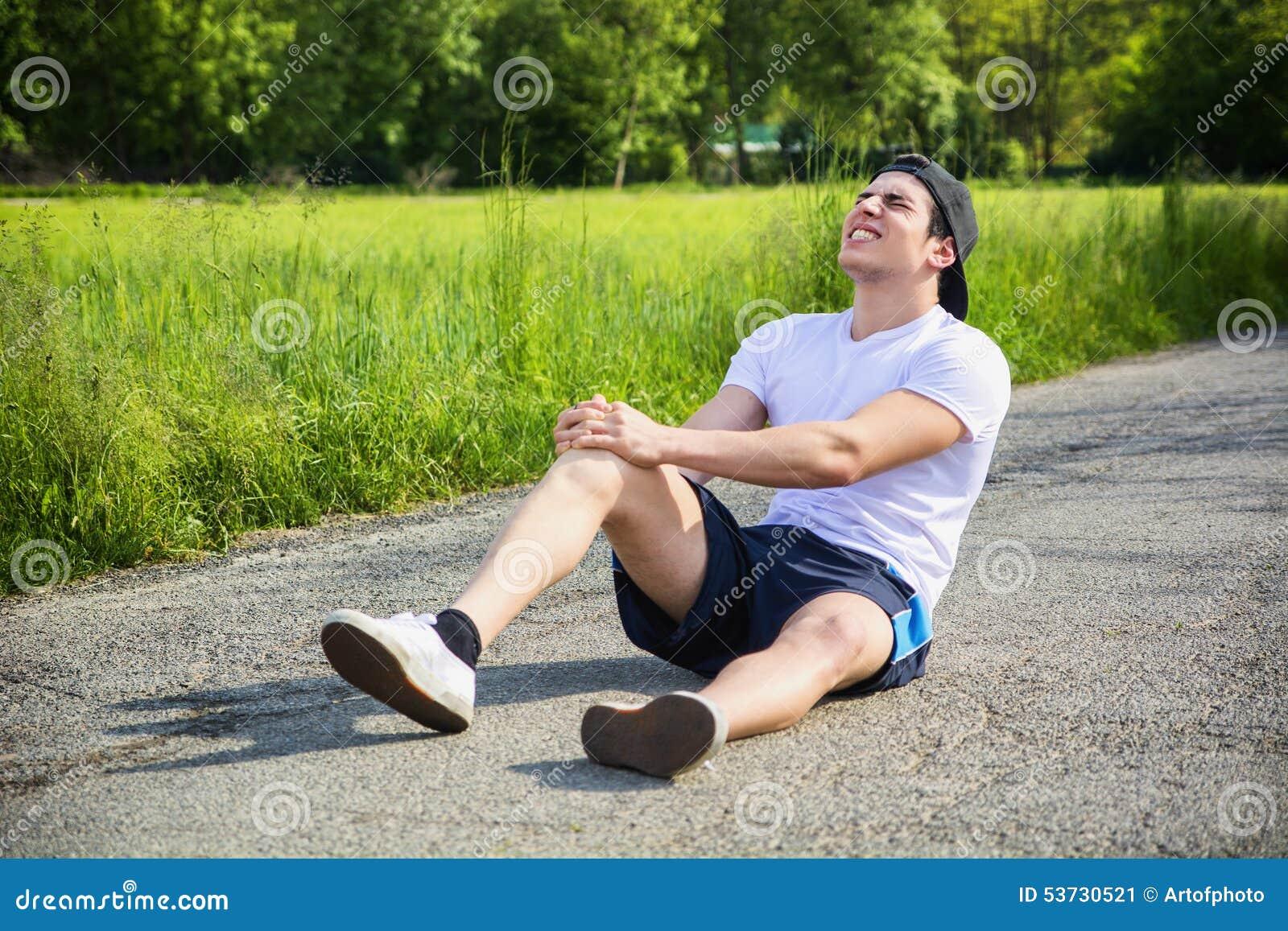 Hübscher junger Mann beim Laufen verletzt und
