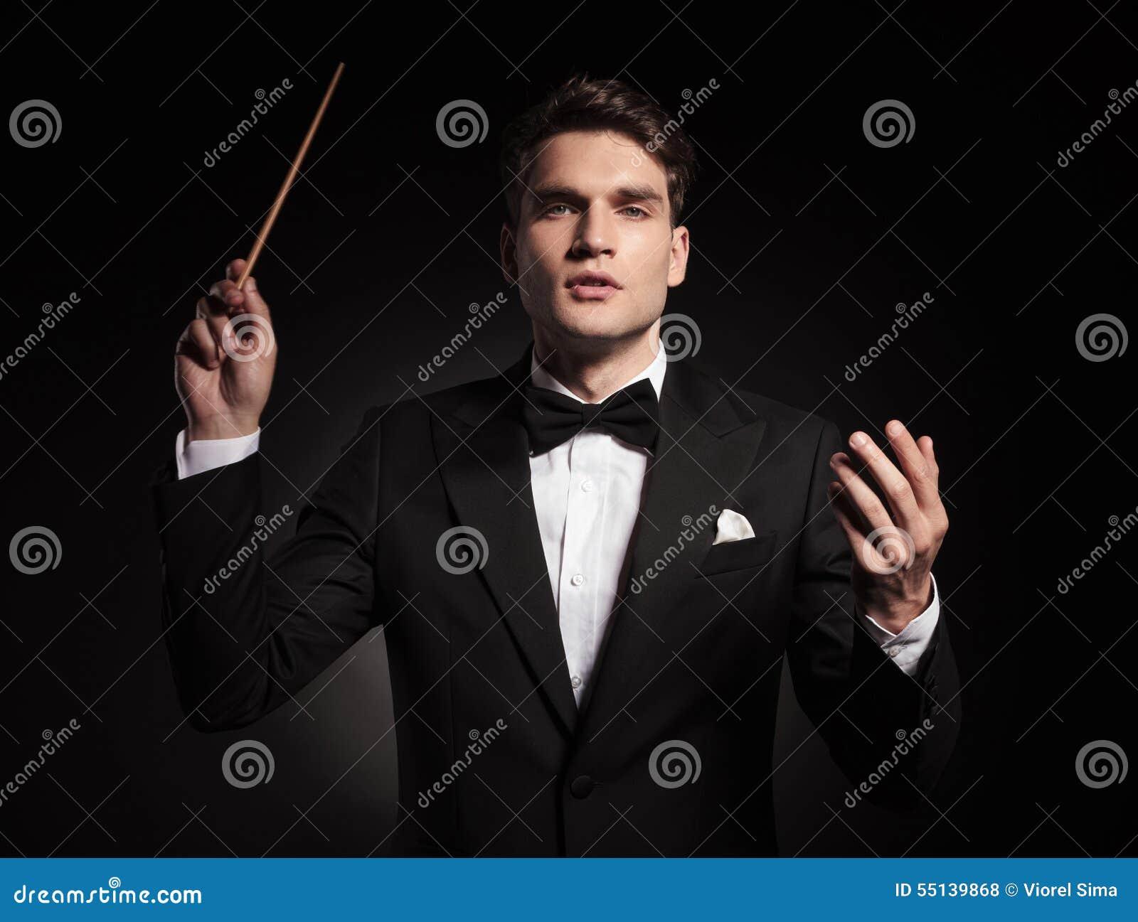 Hübscher junger Mann, der einen Stock in seiner Hand hält