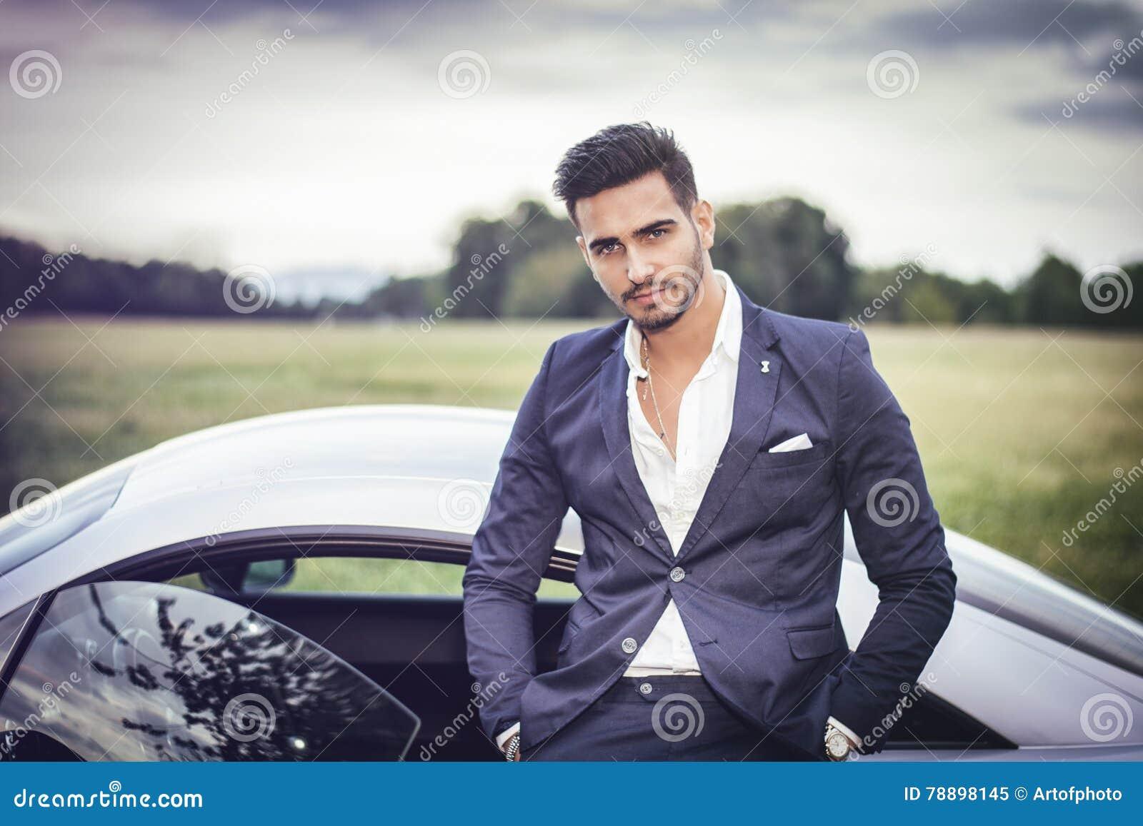 Hübscher junger Mann, der in seinem Auto sitzt