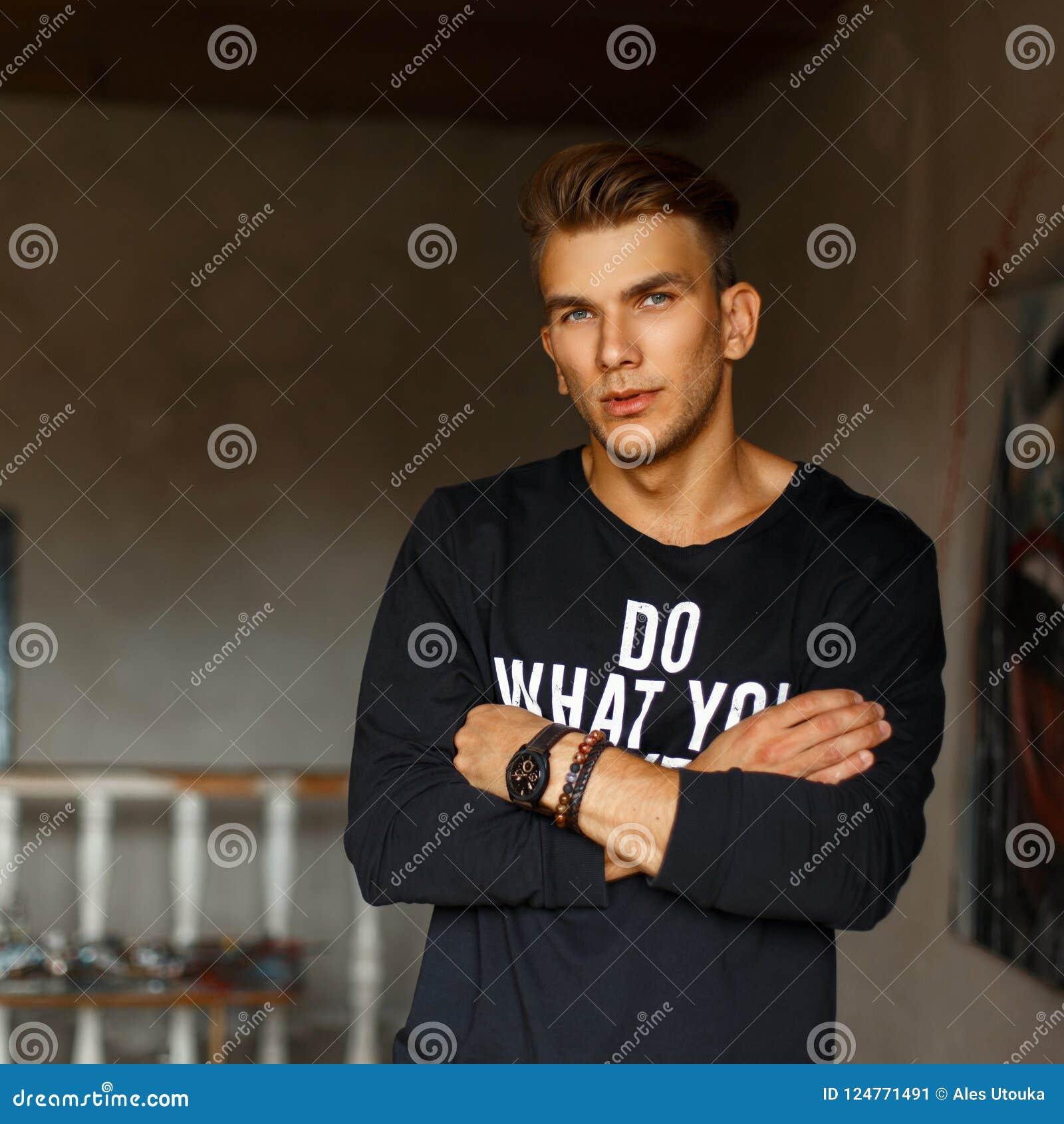 Hübscher junger Mann in einem schwarzen Pullover mit Text im Raum