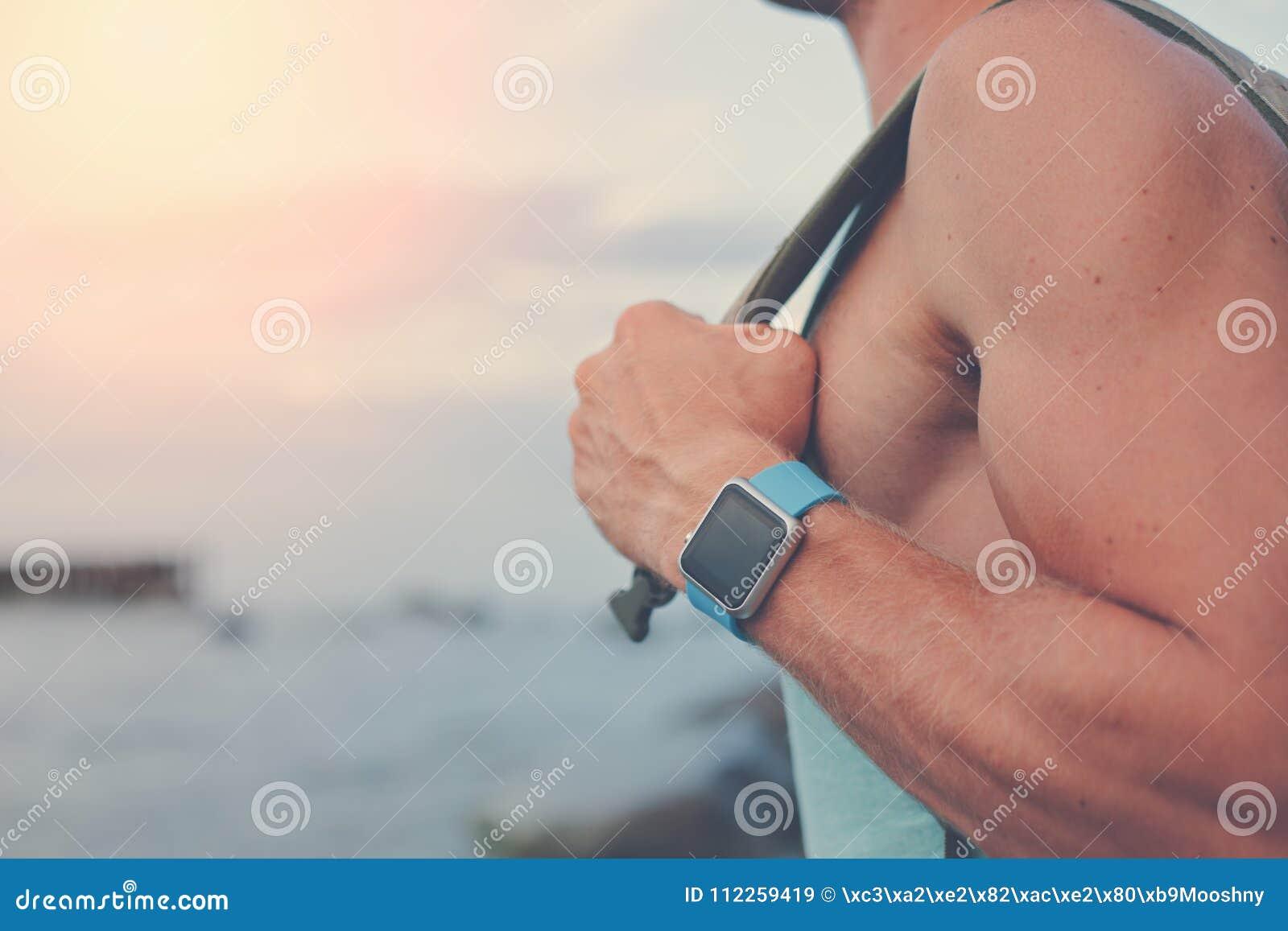 Hübscher junger Mann mit dem Rucksack, der intelligente Uhren nahe dem Ozean trägt