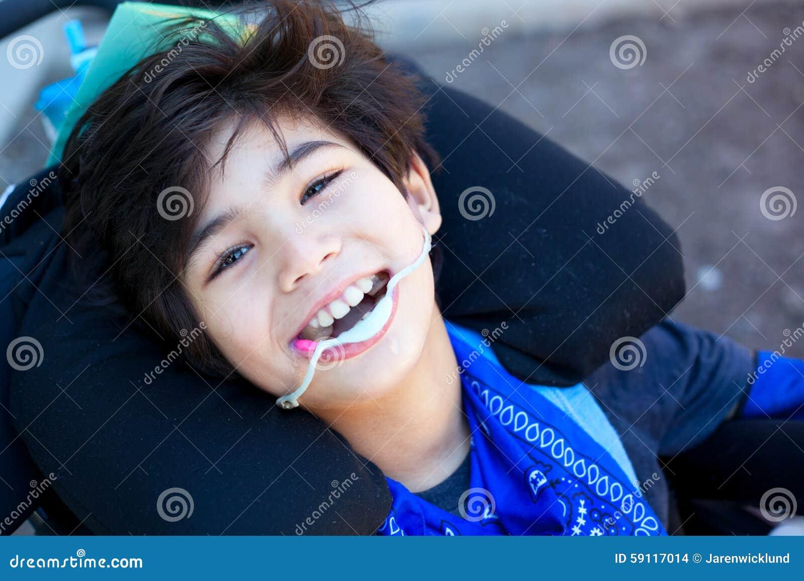 h bscher kleiner behinderter junge im rollstuhl oben l chelnd an der kamera stockfoto bild. Black Bedroom Furniture Sets. Home Design Ideas